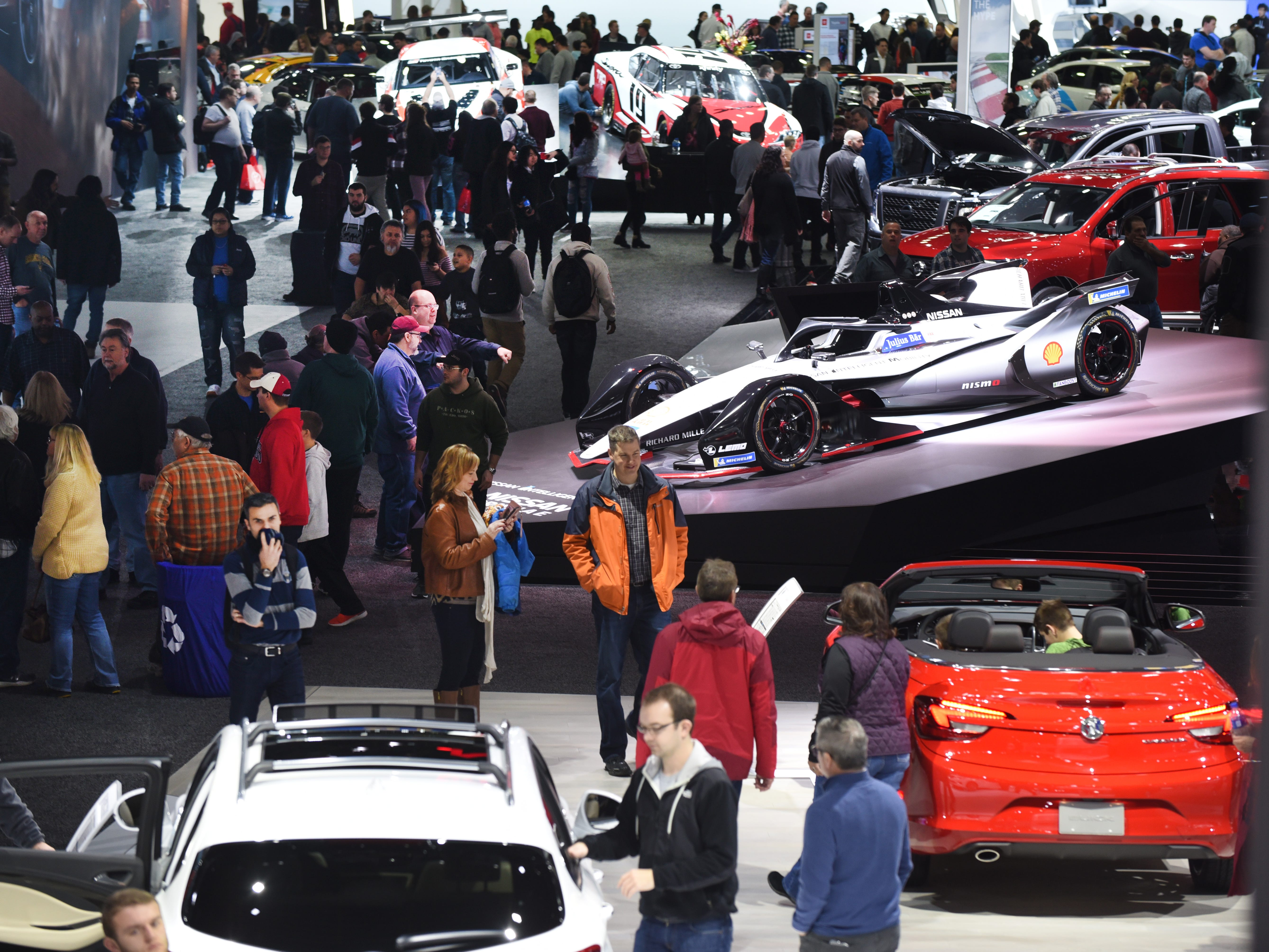 Crowds of people walk through displays at Cobo Center for the 2019 North American International Auto Show on Saturday, January 19, 2019.
