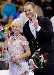 In this Jan. 11, 2014, file photo, bronze medalists Caydee Denney and John Coughlin, of the United States, smile during an award ceremony at the U.S. Figure Skating Championships in Boston. Coughlin, a two-time U.S. pairs champion recently suspended from figure skating, has died.  He was 33.