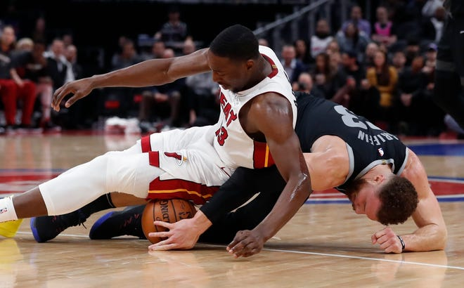 Detroit Pistons forward Blake Griffin (23) and Miami Heat center Bam Adebayo chase the loose ball.