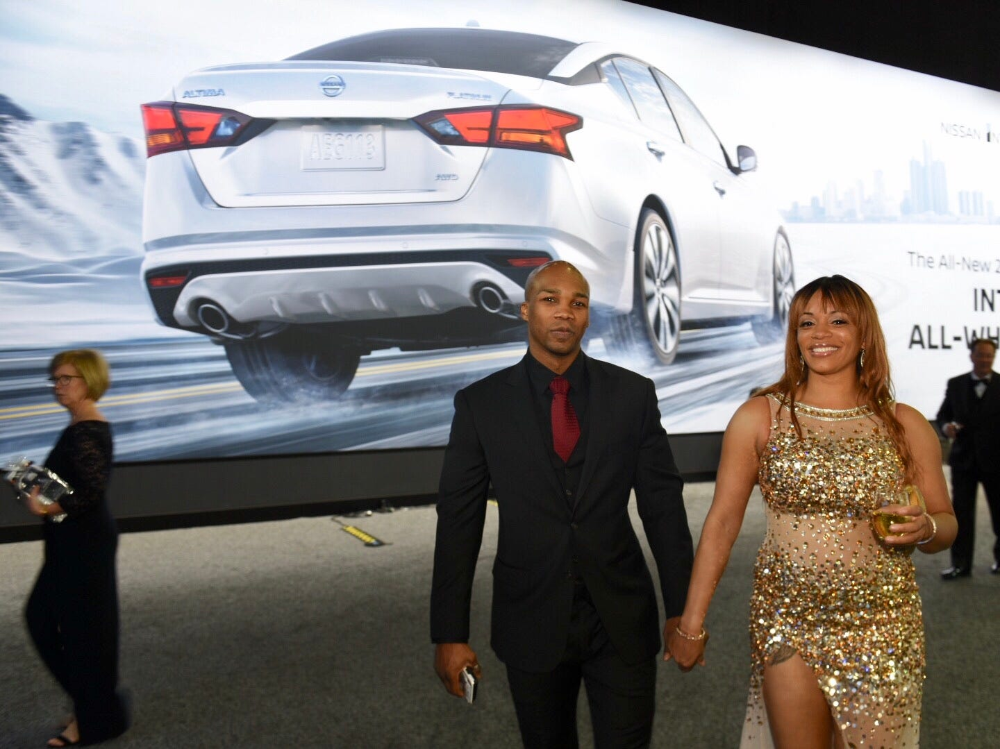 Mike Ejia and Shay Horchata of Las Vegas walk past a billboard-size image of the 2019 Nissan Altima at the Charity Preview.