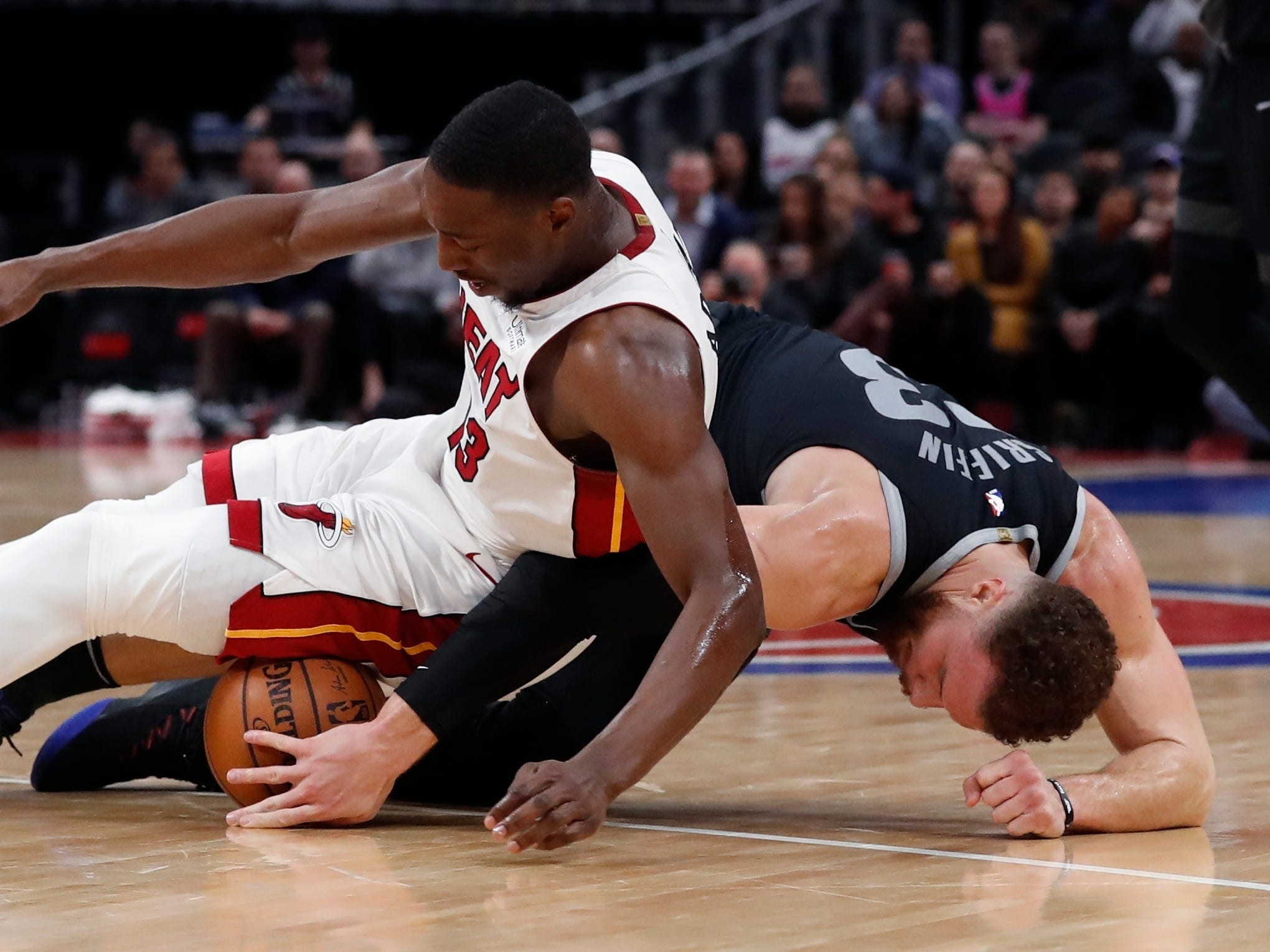 Detroit Pistons forward Blake Griffin (23) and Miami Heat center Bam Adebayo chase the loose ball during the first half.