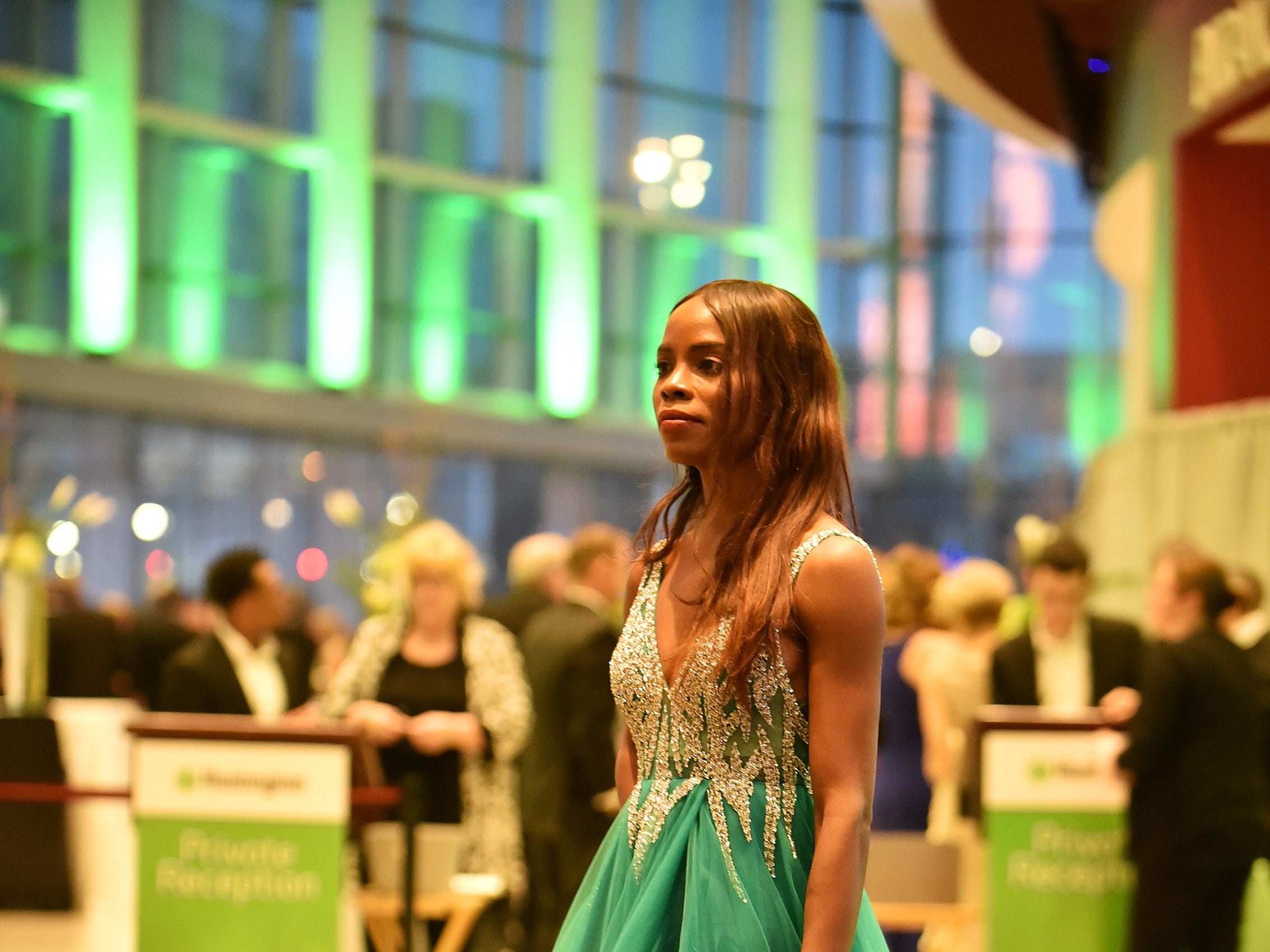 Gloria Tuggle of Lansing, wearing a dress by Jovani, poses for a photo by her husband, Troy Tuggle, not pictured, in the lobby outside the Charity Preview gala in Detroit.