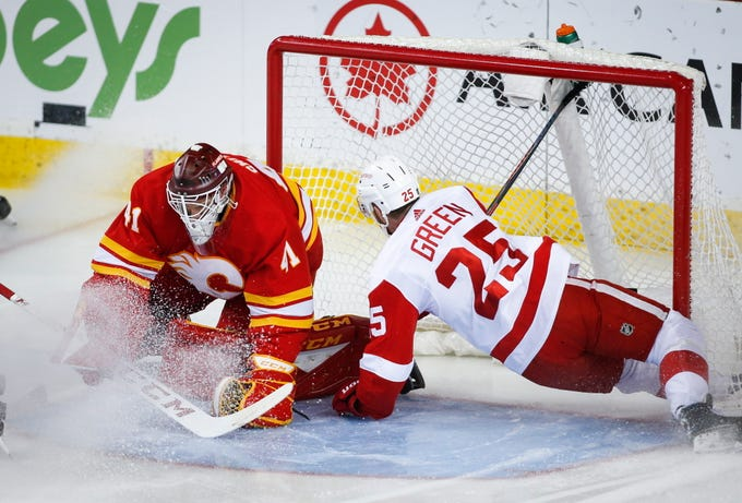 Detroit Red Wings' Mike Green, right, crashes into Calgary Flames goalie Mike Smith during the first period of their hockey game, Friday, Jan. 18, 2019 in Calgary, Alberta, Canada.