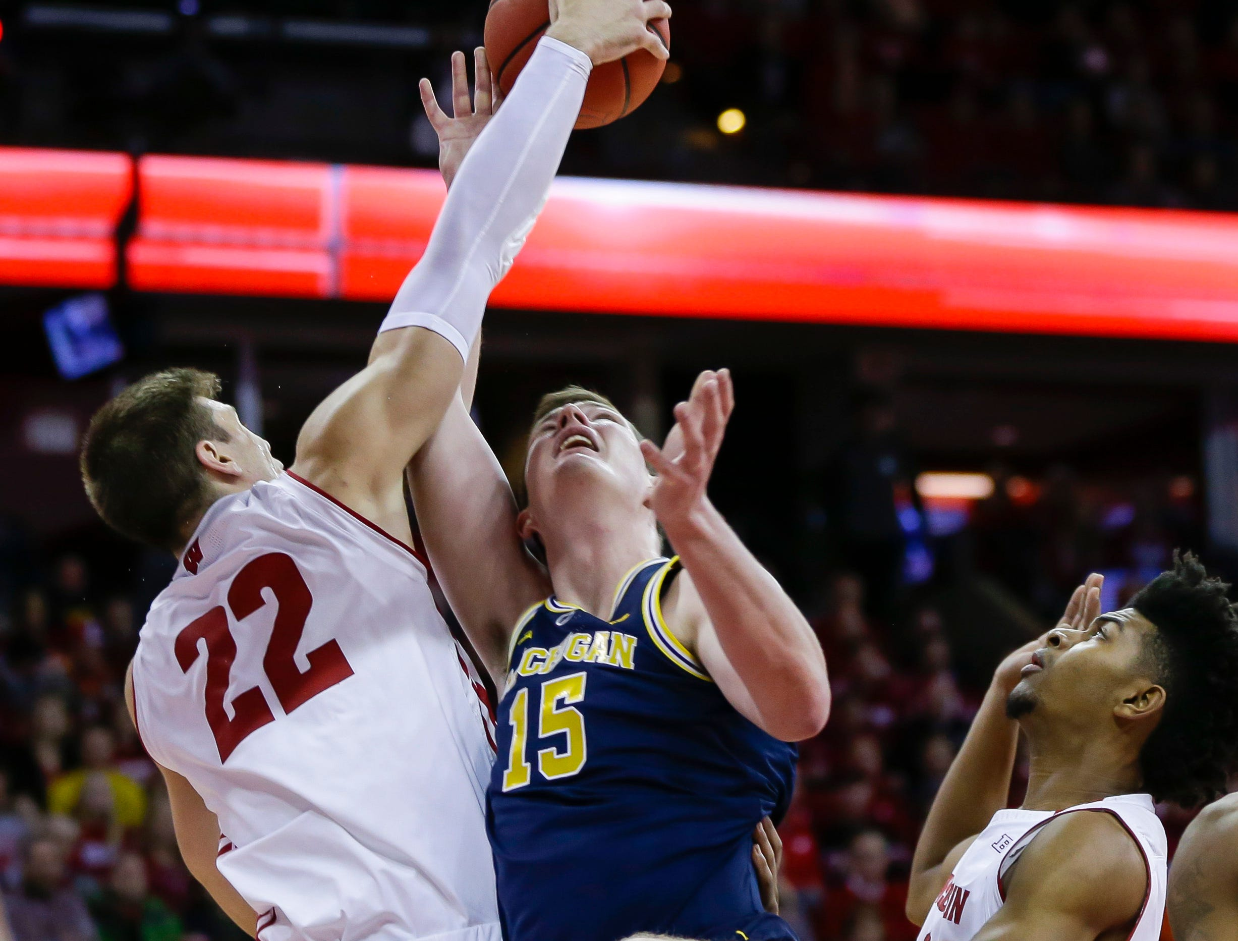 Wisconsin's Ethan Happ (22) and Michigan's Jon Teske (15) battle for a rebound during the first half of an NCAA college basketball game Saturday, Jan. 19, 2019, in Madison, Wis. (AP Photo/Andy Manis)