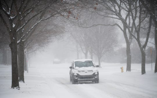 A vehicle drives slowly along a snowy Fairholme Road on Saturday morning in Grosse Pointe Woods.