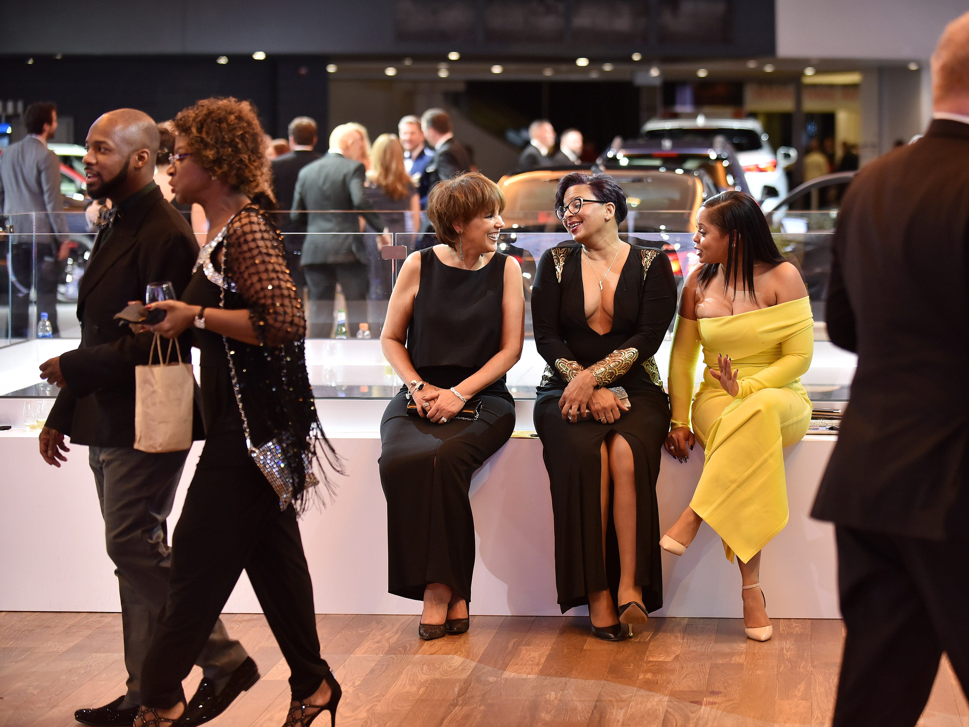 From left, Pam Wood of Farmington Hills, Marie May of Westland and Rhonda Parker of Canton chat near the Chevrolet display at the Charity Preview.