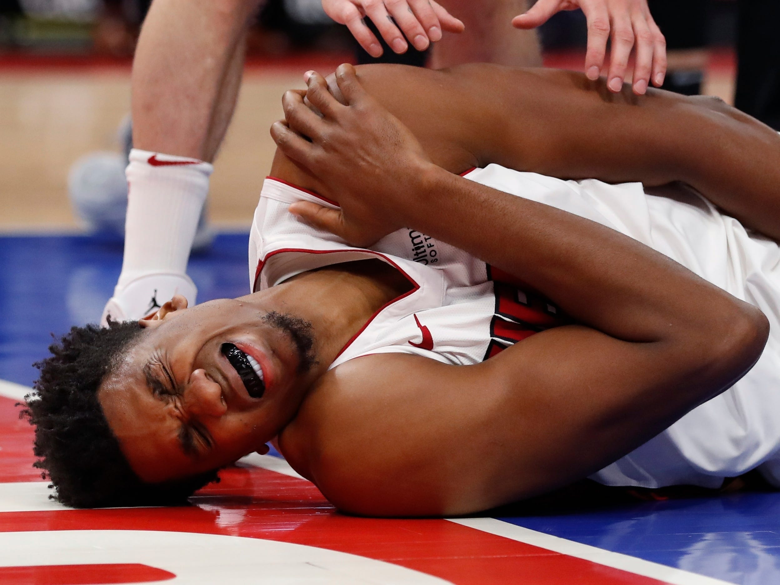 Miami Heat center Hassan Whiteside grimaces after falling on his shoulder after a foul by Detroit Pistons center Zaza Pachulia during the second half.