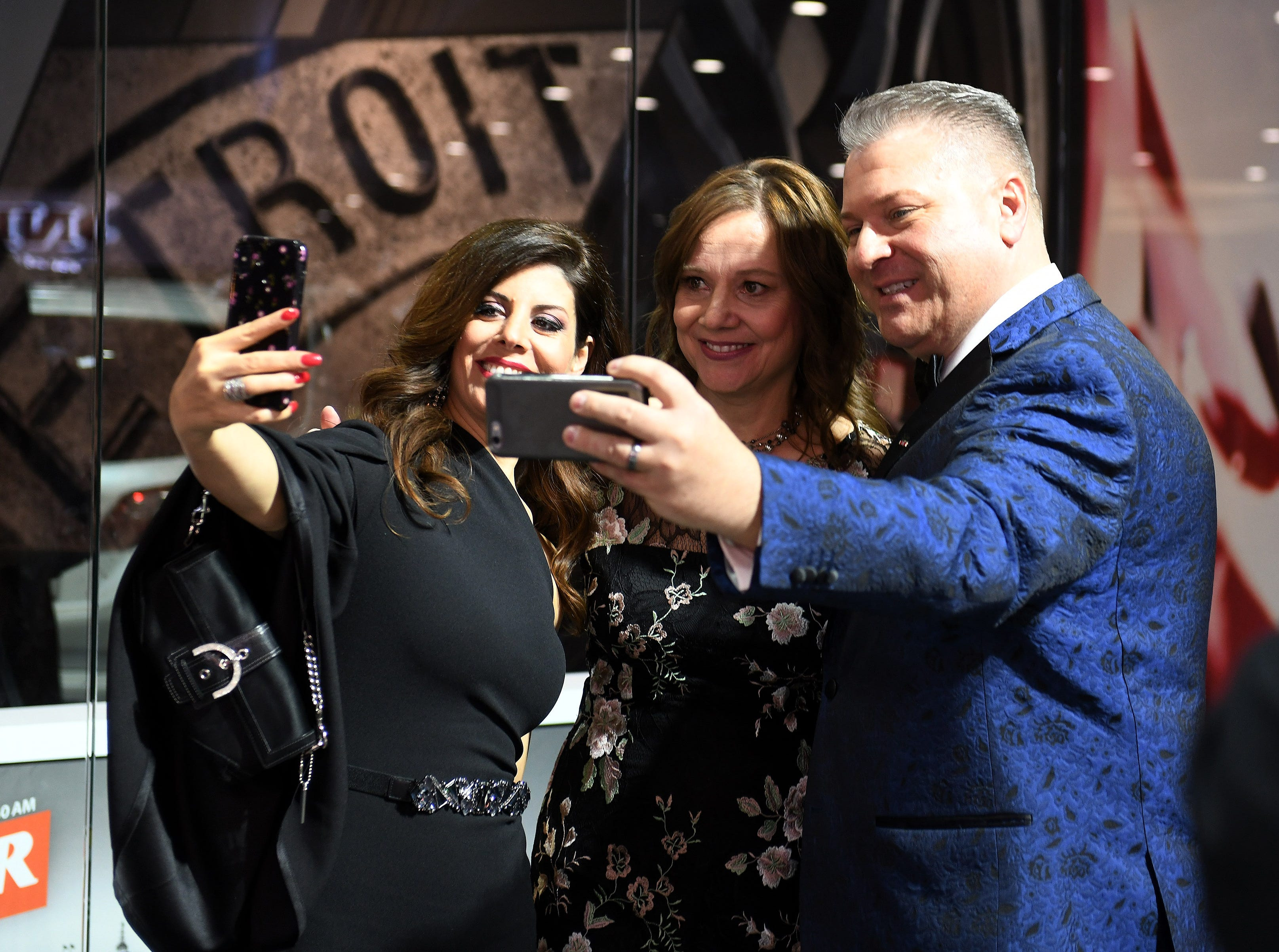 Rocky Raczkowski, right, and his wife, Amalia Raczkowski, left, both takes selfies with GM Chairwoman and CEO Mary Barra at the Charity Preview.