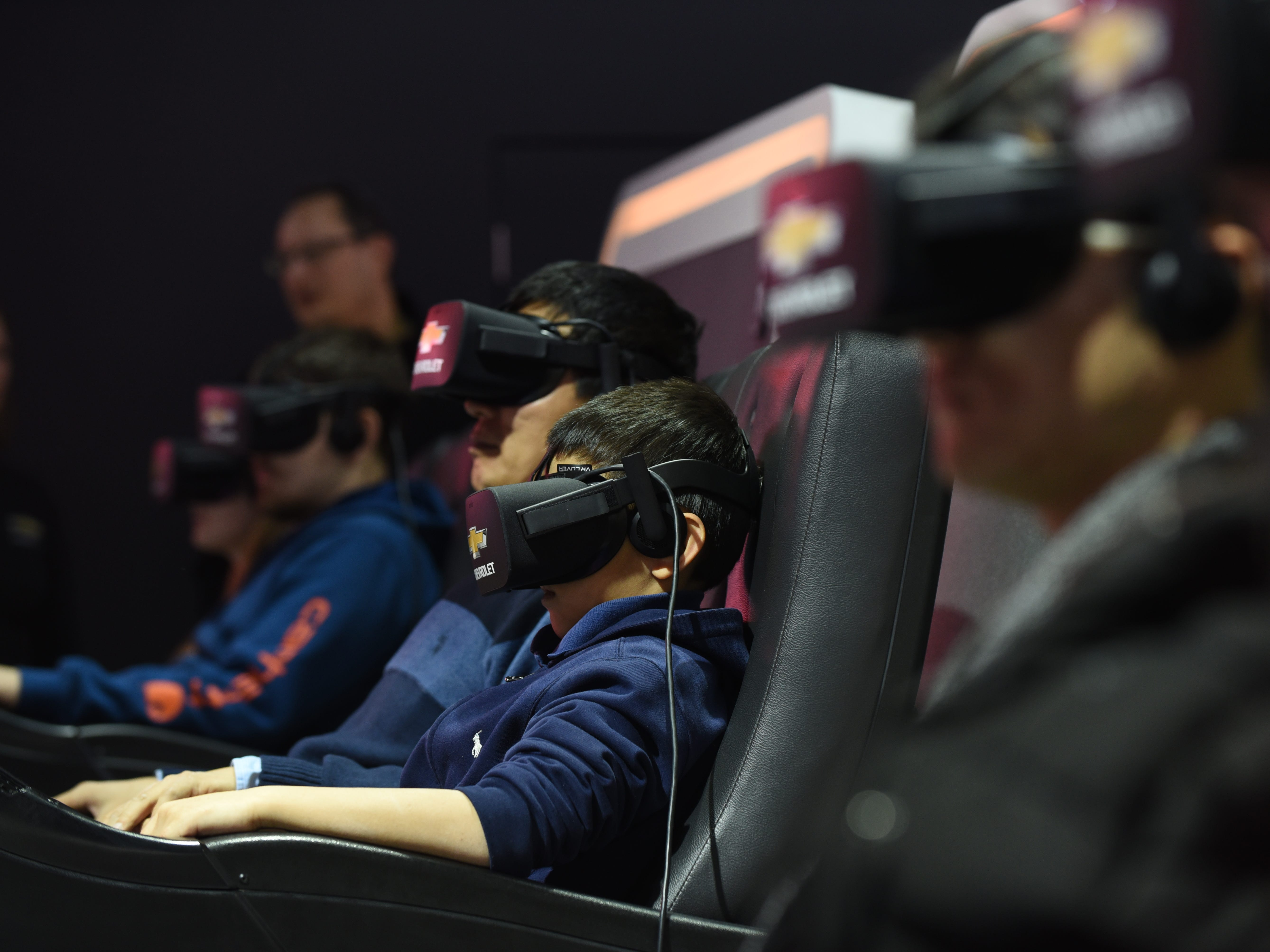 People wear VR headgear at General Motors Virtual Dynamics Lab 4D Experience at the 2019 North American International Auto Show on Saturday, January 19, 2019 .