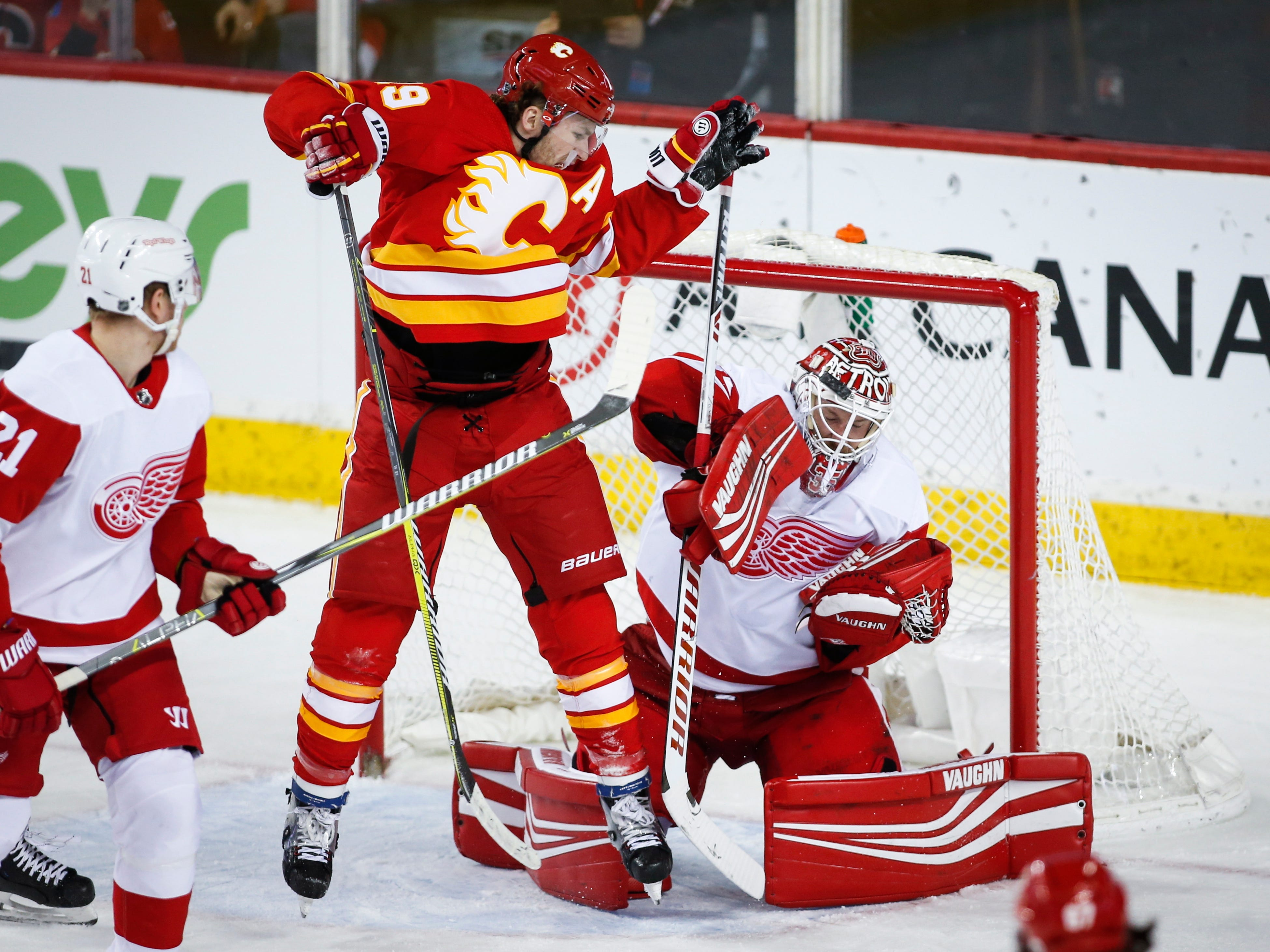 Red Wings goalie Jimmy Howard, right, has his shot deflect off his helmet as the Flames' Matthew Tkachuk jumps during the second period.