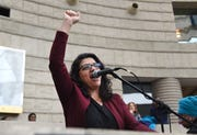 U.S. Rep. Rashida Tlaib, D-Detroit,  raised her fist in solidarity in front of hundreds gather at the Charles Wright Museum of African American History for the Women's March Michigan