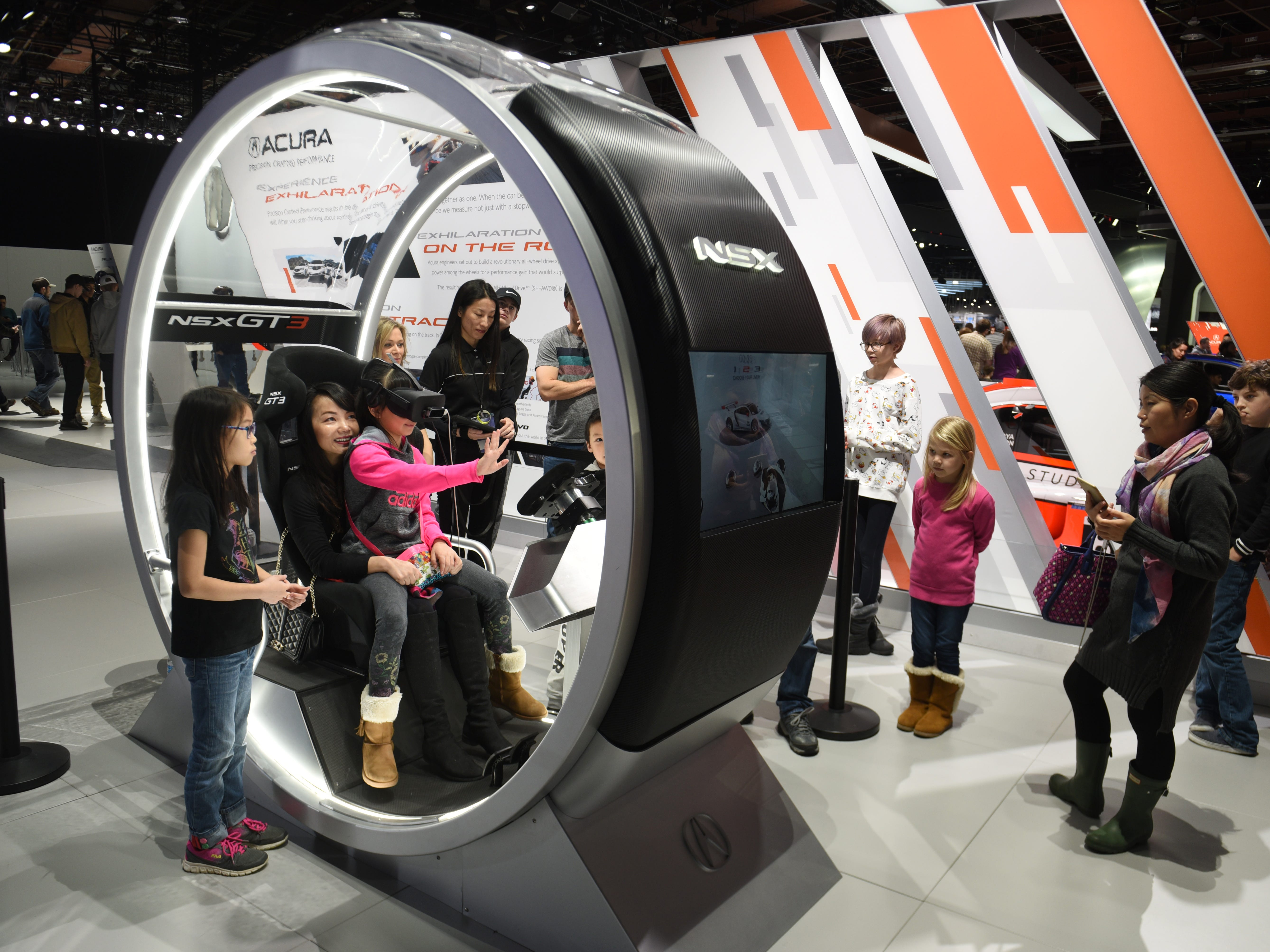 Fiona Tian, 9, sits on the lap of Tingting Yan as they enjoy the Acura GT3 virtual reality simulator on Saturday, January 19, 2019.