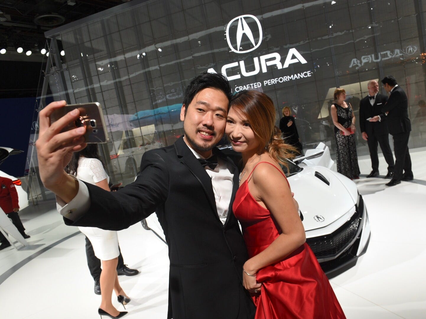Mark Lu and wife Joey of Houston, Texas, snap a selfie at Acura NSX display at the 2019 Charity Preview on Friday, Jan. 18.