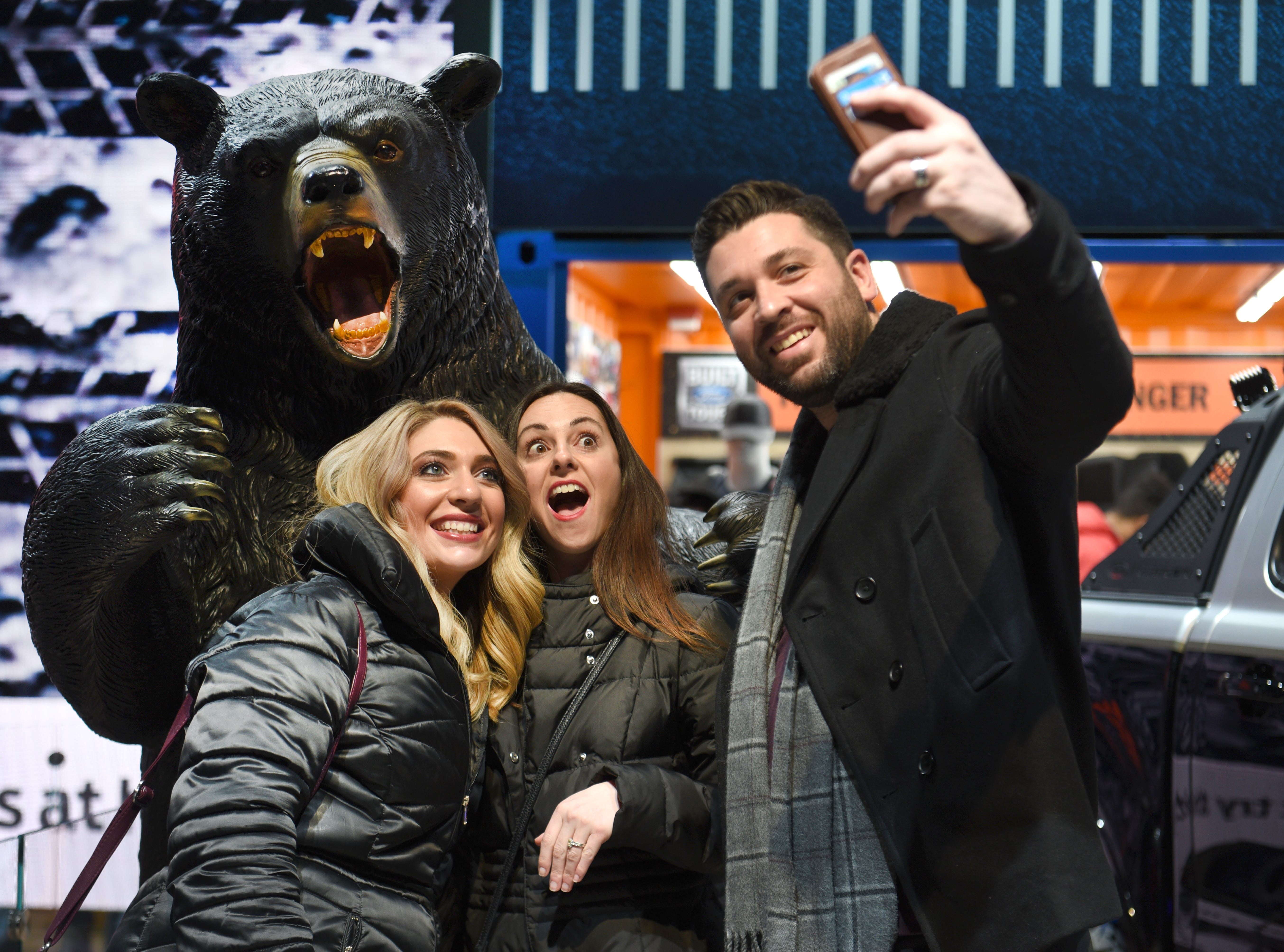 Jonathan Burgio (right) snaps a photograph with his sister Alysia Burgio (left) and his wife Amy Burgio with a grizzly bear at the Ford Motor Company display during the 2019 North American International Auto Show on Saturday, January 19, 2019.