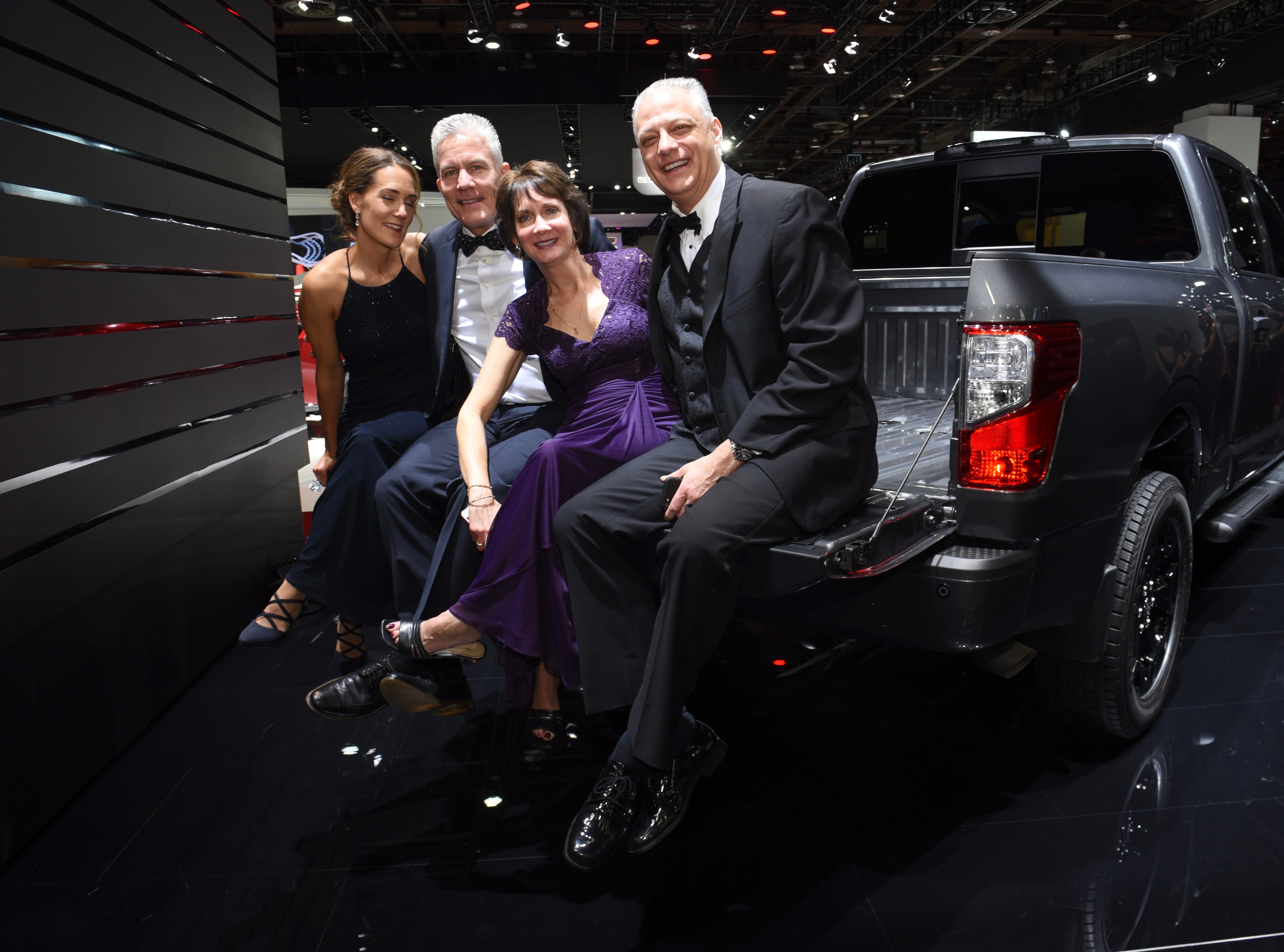 From left, Kelly and Mathew Gajda share a moment on the tailgate of a Nissan Titan XD with Lesa Melhorn and her husband Marty.