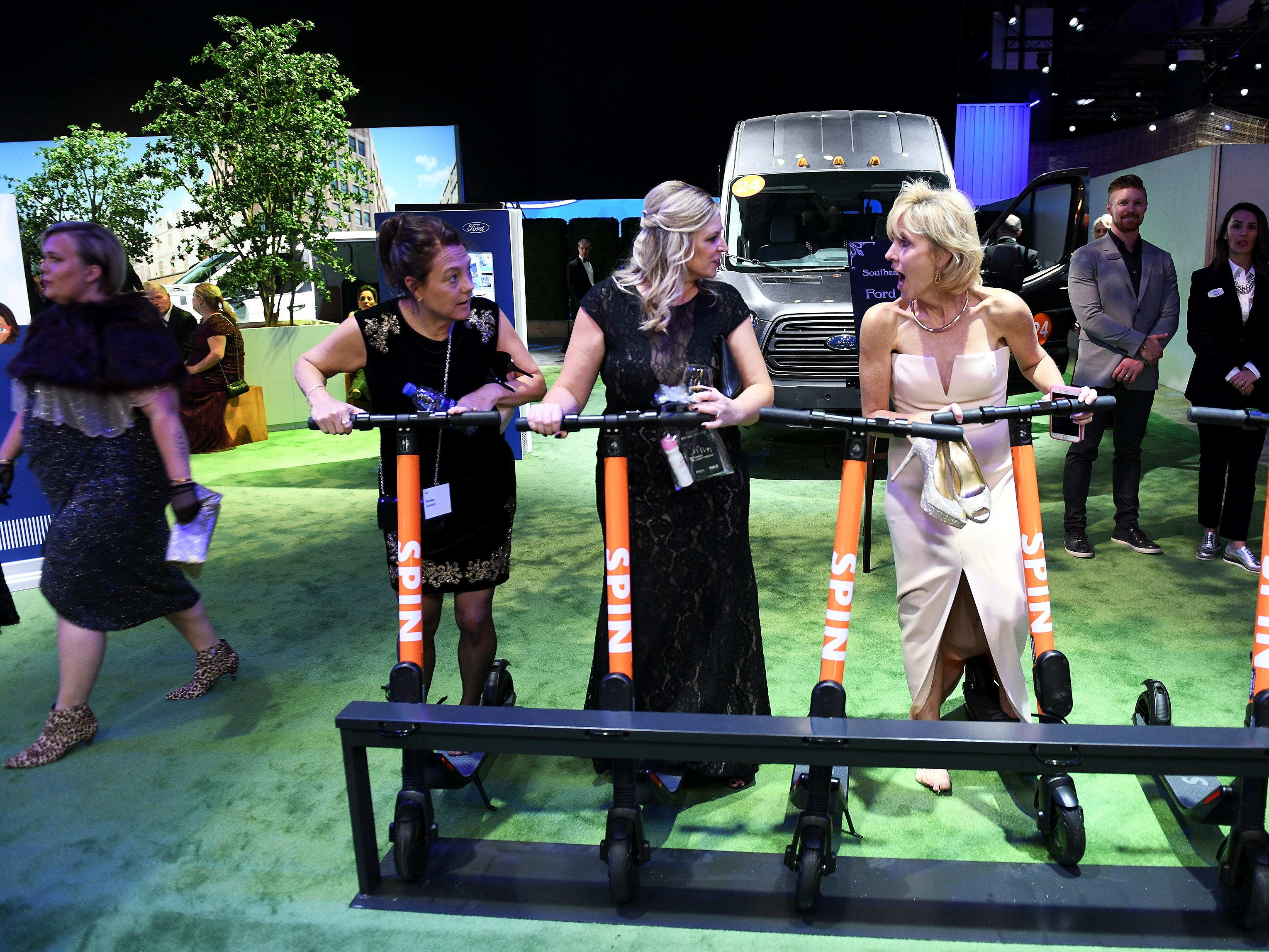 From left, Shelley Catalan of Ann Arbor, Kelly Hollis Brown of Northville and Colleen Luck of Mount Clemens check out Spin scooters at the Ford exhibit.