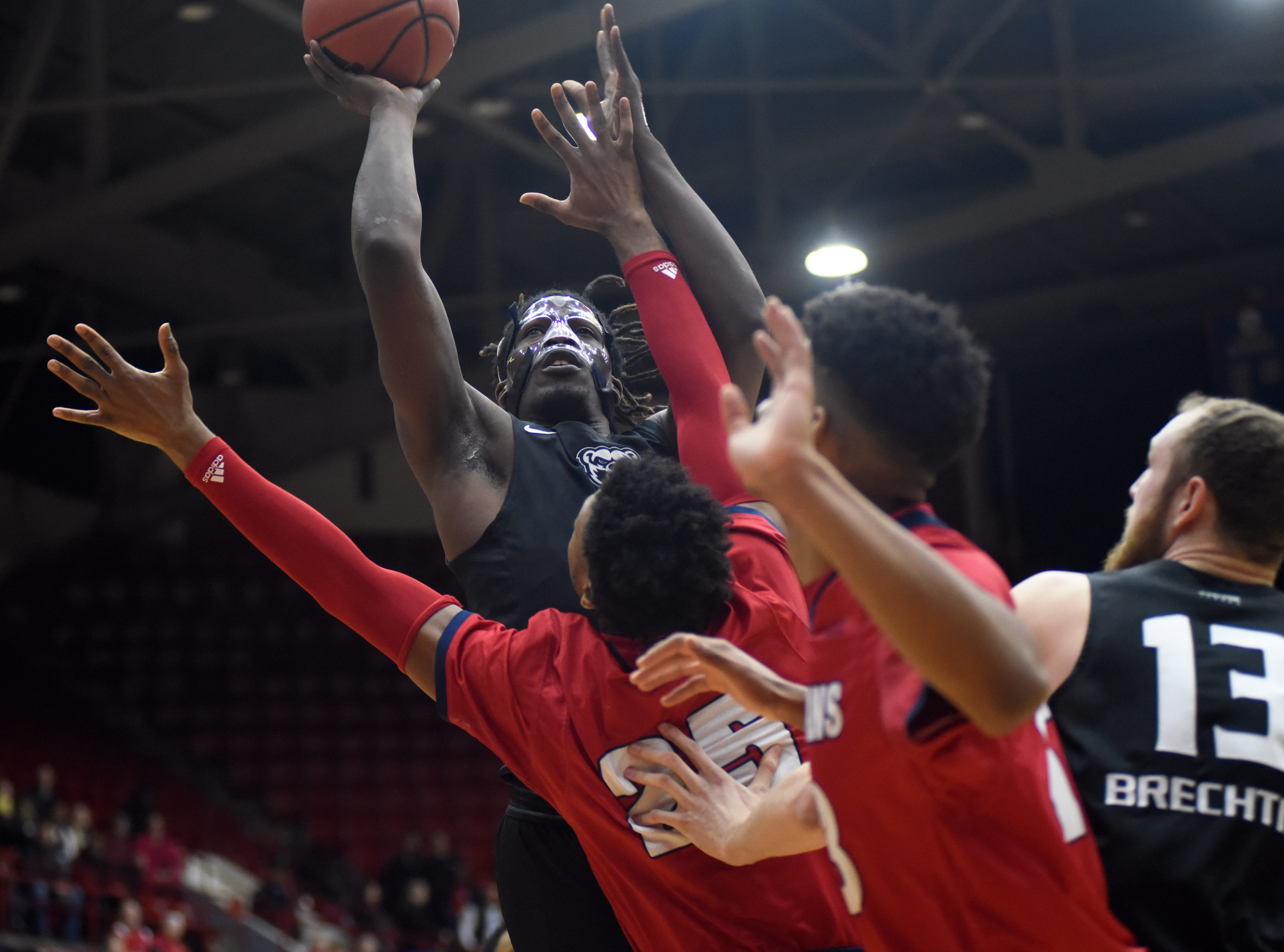 Oakland Golden Grizzlies forward Xavier Hill-Mais (14), top, goes up for a basket against the Detroit Titans in the first half, Saturday, Jan. 19, 2019, at Calihan Hall in Detroit.  (Jose Juarez/Special to Detroit News)