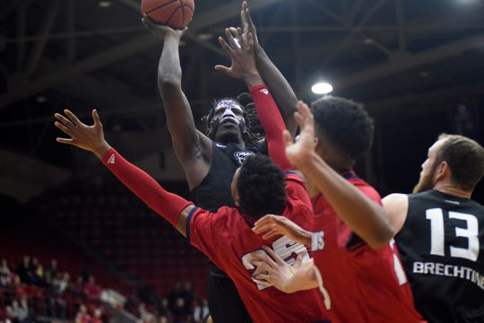 Oakland Golden Grizzlies forward Xavier Hill-Mais (14), top, goes up for a basket against the Detroit Titans in the first half. Hill-Mais finished with 22 points in Oakland's 79-73 victory Saturday at Calihan Hall.