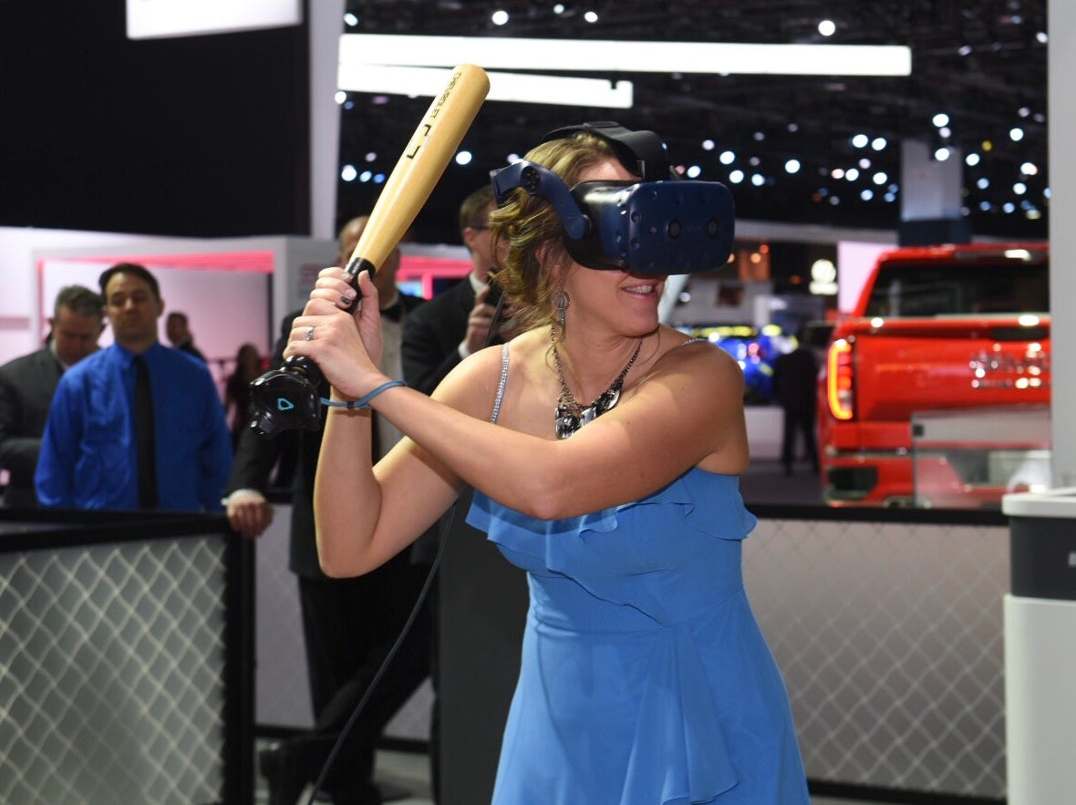 Jennifer Buikema of Kalamazoo, Michigan, takes a swing in her evening dress at the General Motors batting simulator during the Charity Preview gala.
