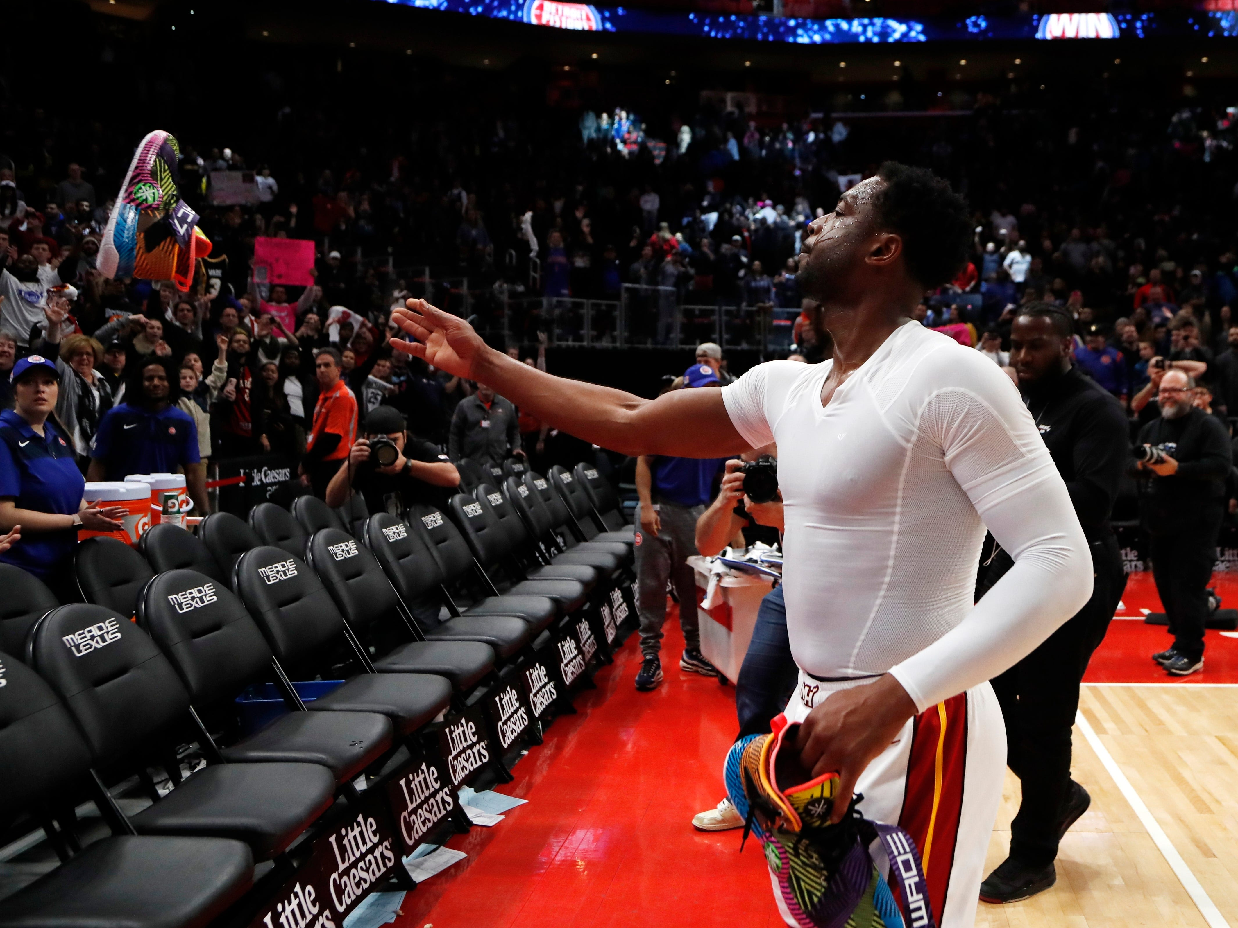 Miami Heat guard Dwyane Wade tosses one of his sneakers to a fan after the game.