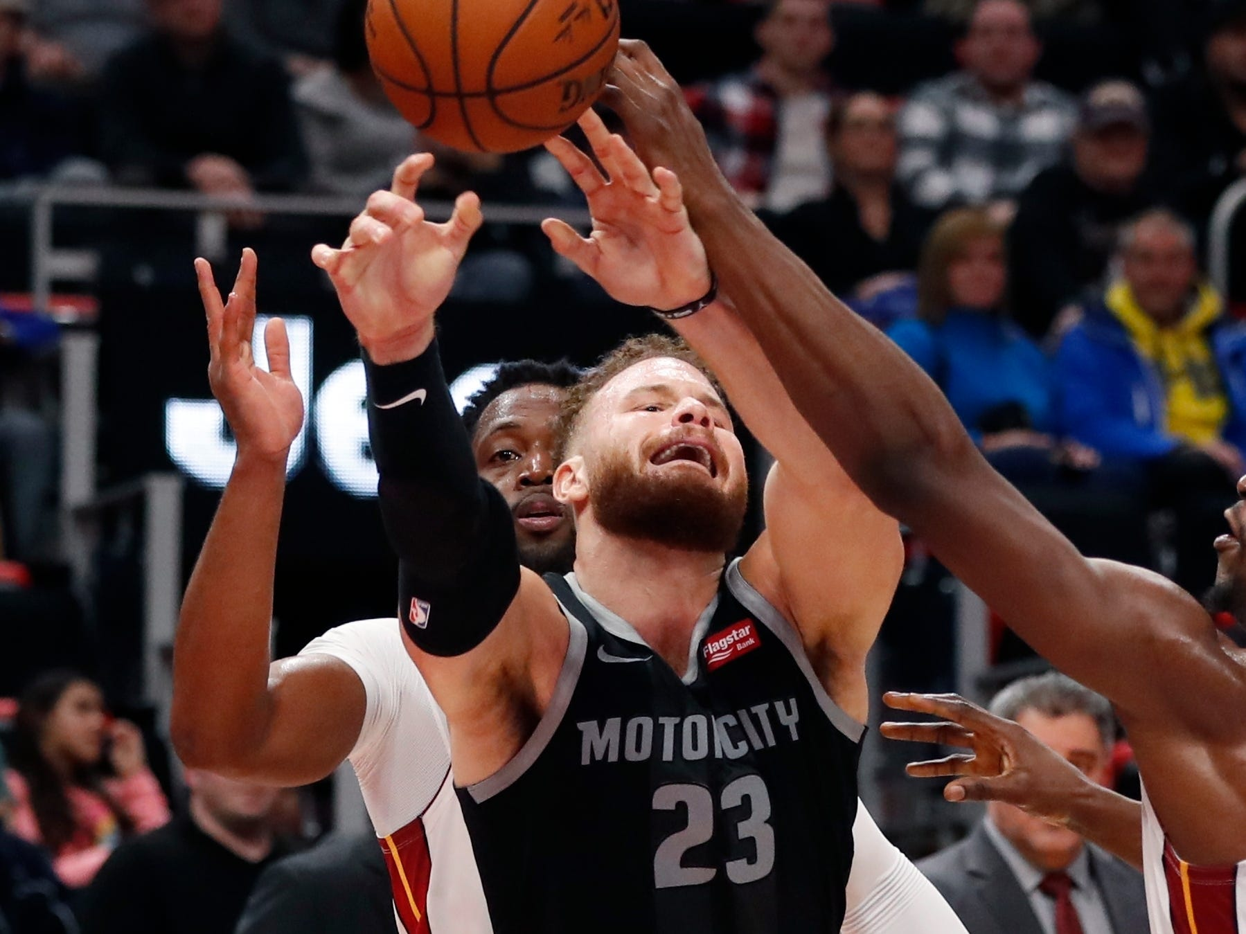 Detroit Pistons forward Blake Griffin (23) loses control of the ball as Miami Heat guard Dwyane Wade, rear, and center Bam Adebayo, right, defend during the second half.
