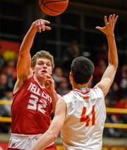Tell City's Braeden Beard (32)] passes over Mater Dei's Andy Heldman (41) as the Mater Dei Wildcats play the Tell City Marksmen at Mater Dei Friday, January 18, 2019.