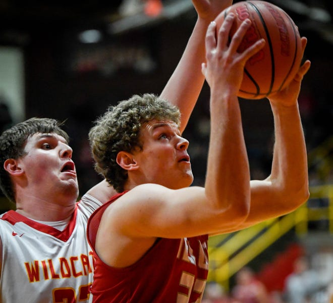 Tell City's Braeden Beard (32) shoots past defense from Mater Dei's Logan Carter (23) as the Mater Dei Wildcats play the Tell City Marksmen at Mater Dei Friday, January 18, 2019.
