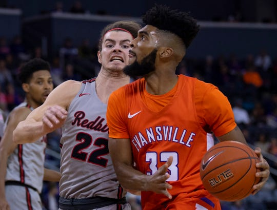 University of Evansville's K.J. Riley (33) drives the baseline while defended by Illinois State's Matt Chastain at Ford Center in January.