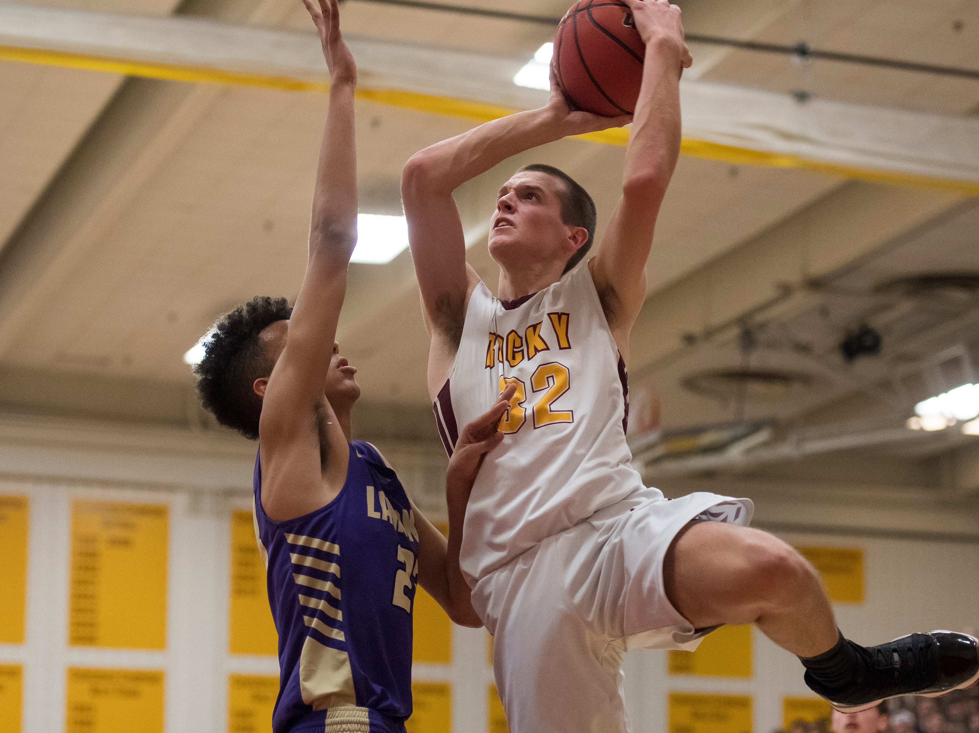 Rocky Mountain High School junior Kenan Schuler (32) puts a shot over Fort Collins High School sophomore Dante Smith (23) on Friday, Jan. 18, 2019, at Rocky Mountain High School in Fort Collins, Colo.