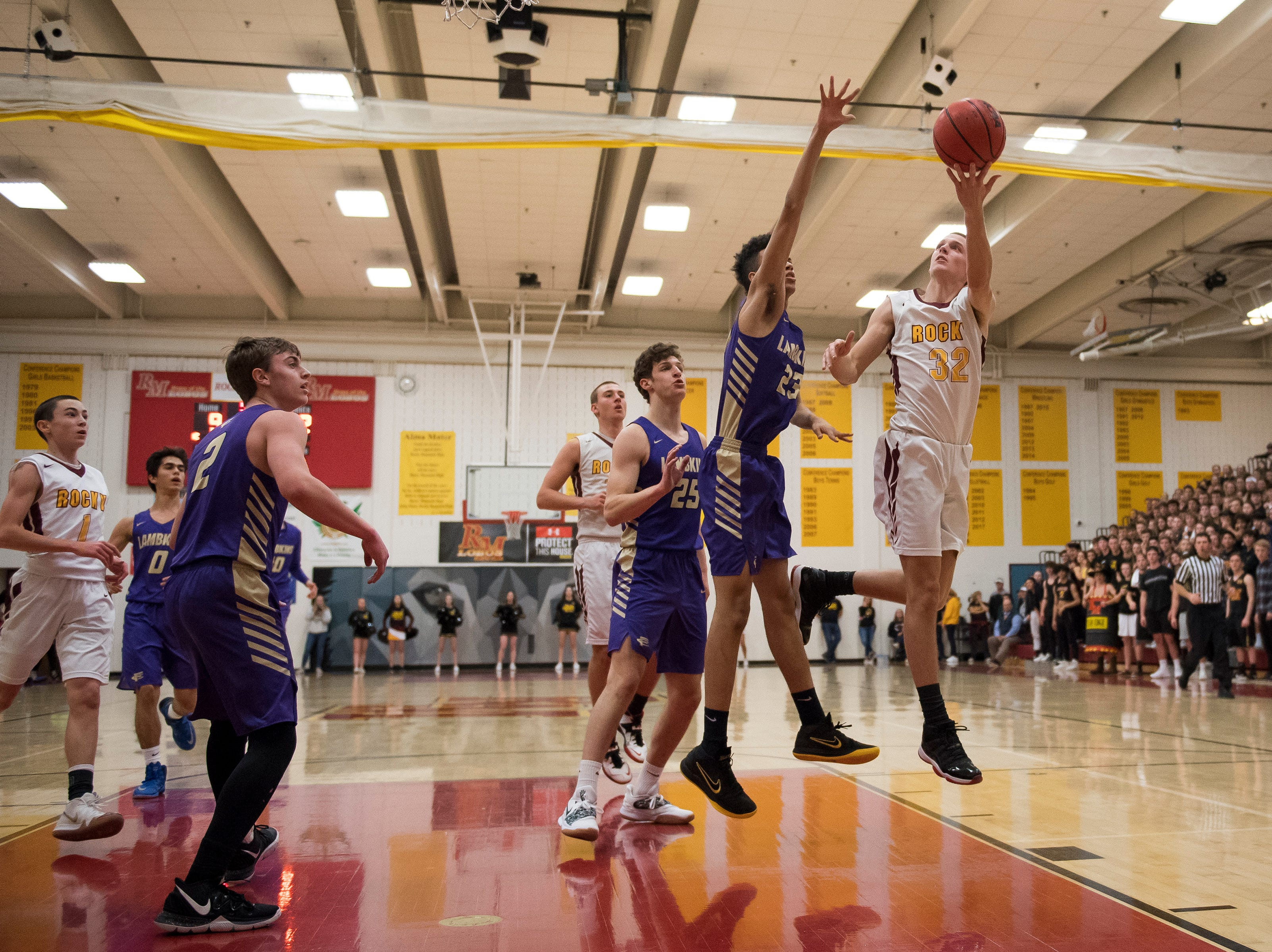 Rocky Mountain High School junior Kenan Schuler (32) puts a shot over Fort Collins High School sophomore Danté Smith (23) on Friday, Jan. 18, 2019, at Rocky Mountain High School in Fort Collins, Colo.