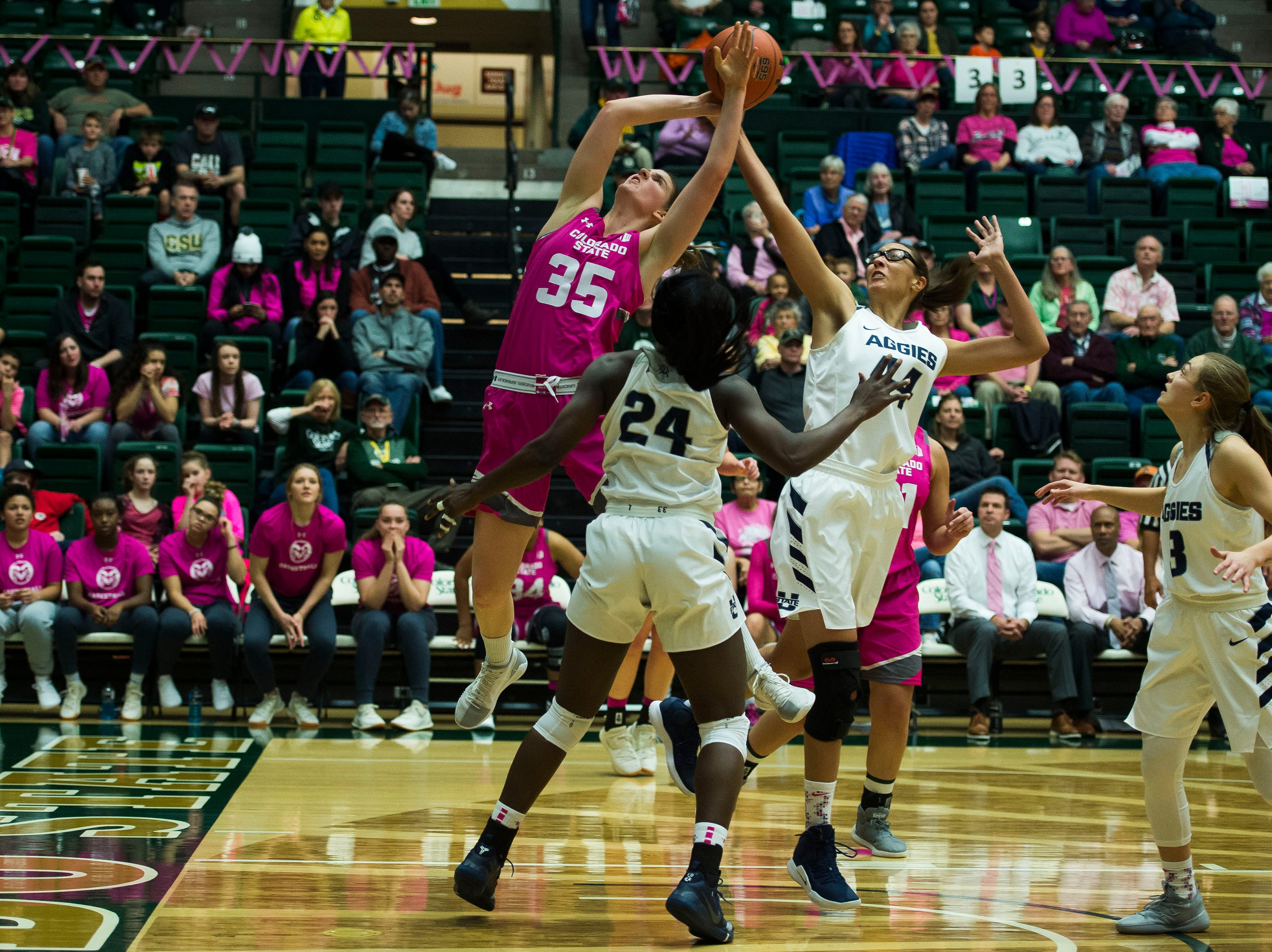 Colorado State University sophomore guard Lore Davis (35) has a shot knocked off-target by Utah State senior center Deja Mason (44) on Saturday, Jan. 19, 2019, at Moby Arena in Fort Collins, Colo.