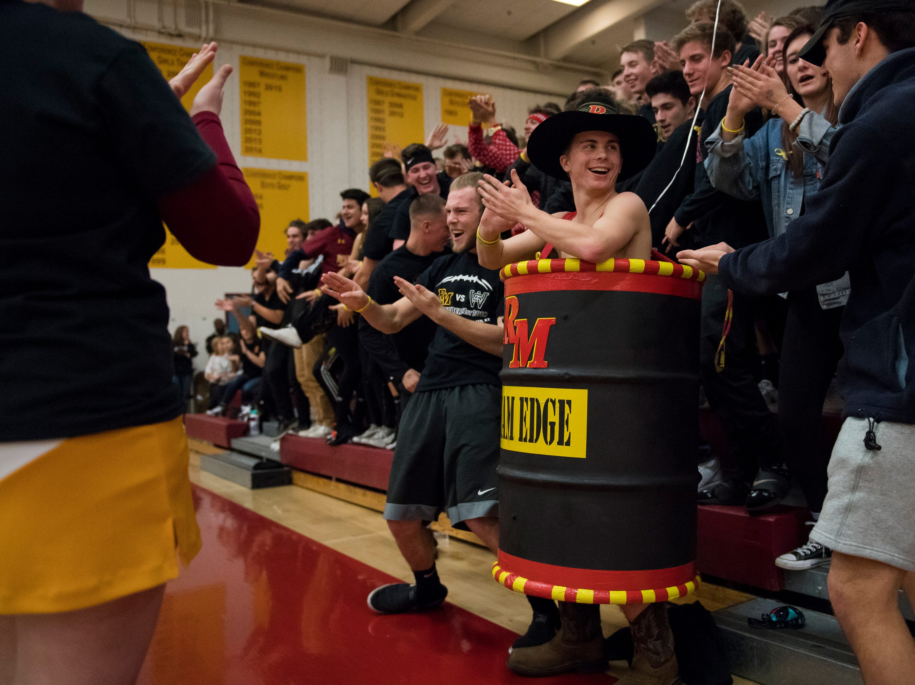 """Rocky Mountain High School senior Conner Culhane celebrates with the student section while wearing """"Team Edge"""" barrel during a game against Fort Collins High School on Friday, Jan. 18, 2019, at Rocky Mountain High School in Fort Collins, Colo."""