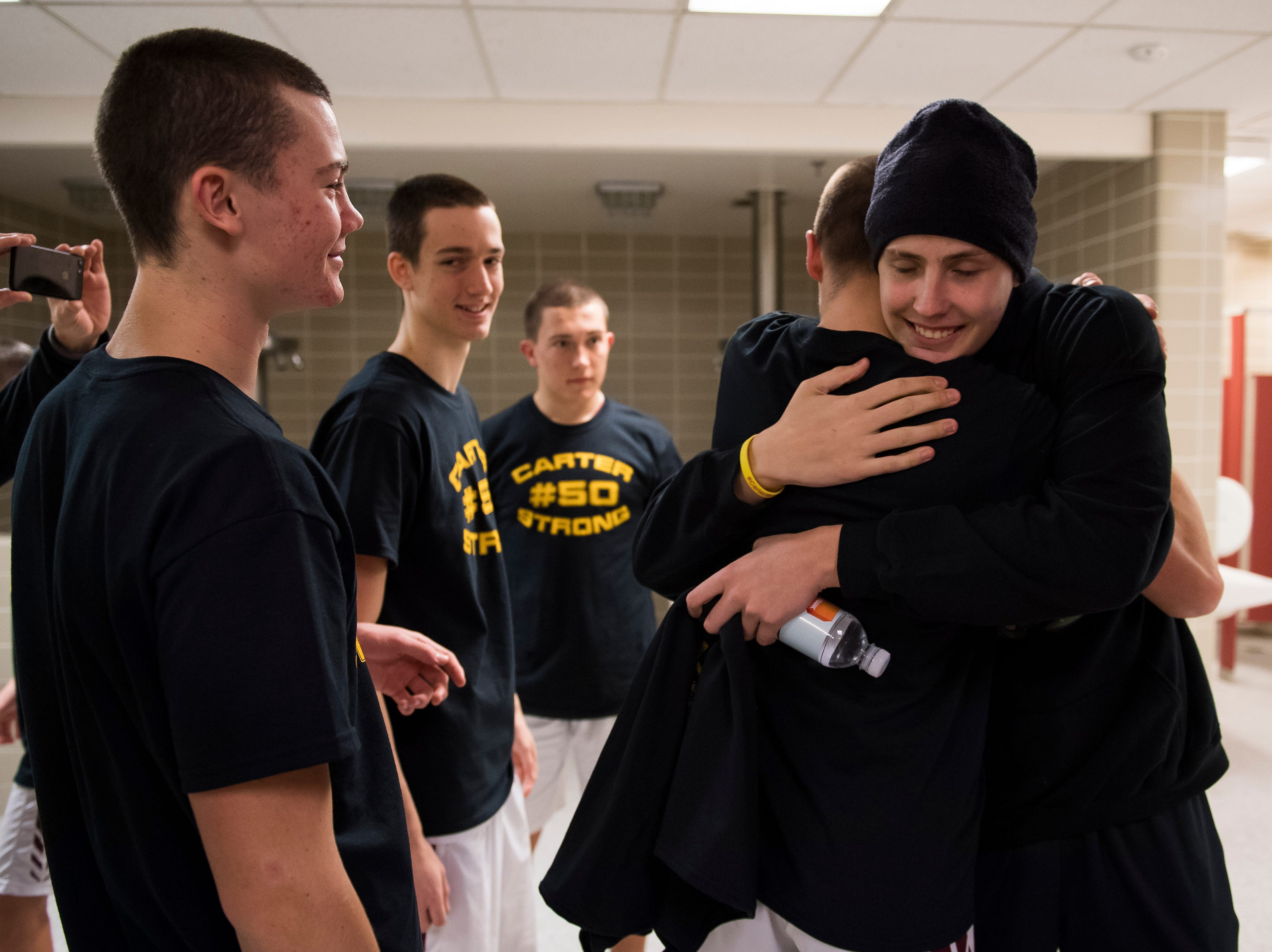Rocky Mountain High School senior Carter Edgerley (50) hugs his teammates in the lockeroom before a game against rival Fort Collins High School on Friday, Jan. 18, 2019, at Rocky Mountain High School in Fort Collins, Colo.