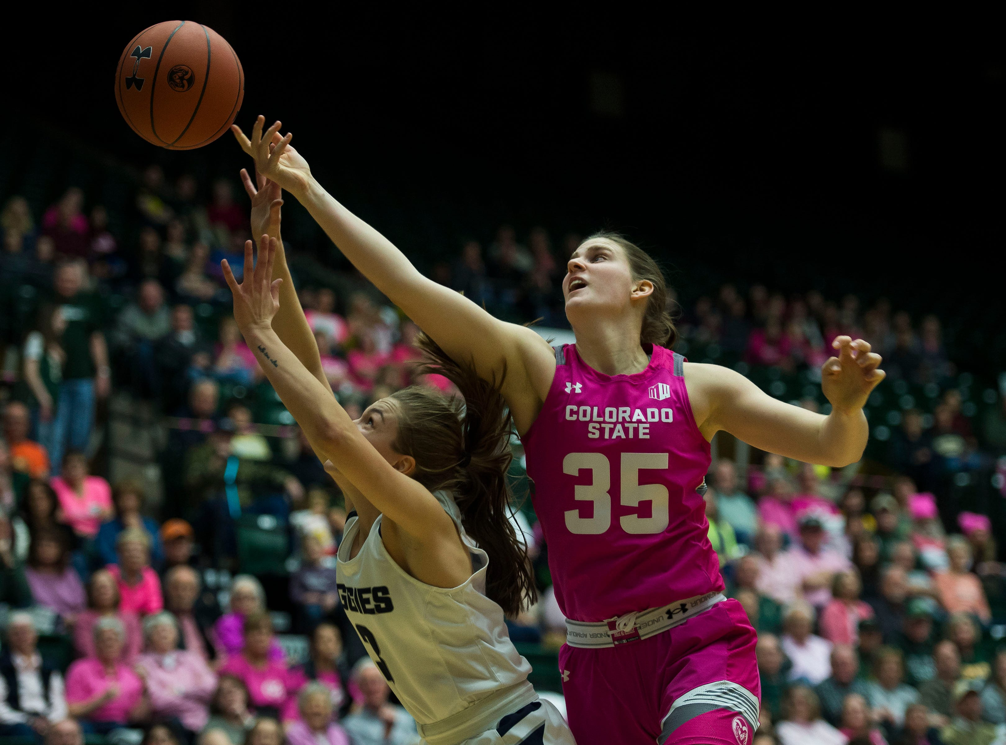 Colorado State University sophomore guard Lore Davis (35) attempts to put a layup over Utah State senior guard Olivia West (3) on Saturday, Jan. 19, 2019, at Moby Arena in Fort Collins, Colo.