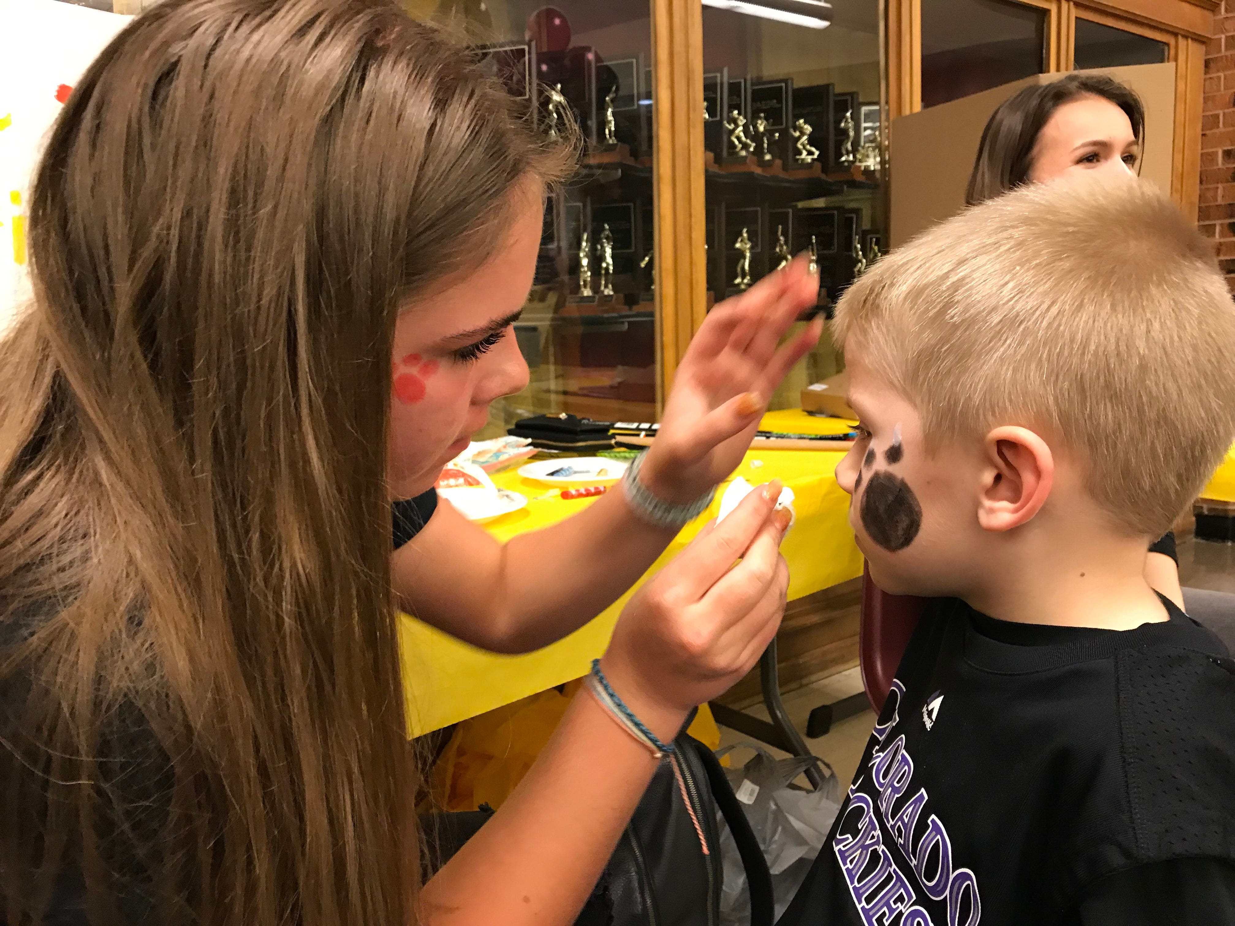 A child gets his face painted as part of the festivities supporting Carter Edgerley, a senior basketball player at Rocky Mountain High School who is battling cancer.