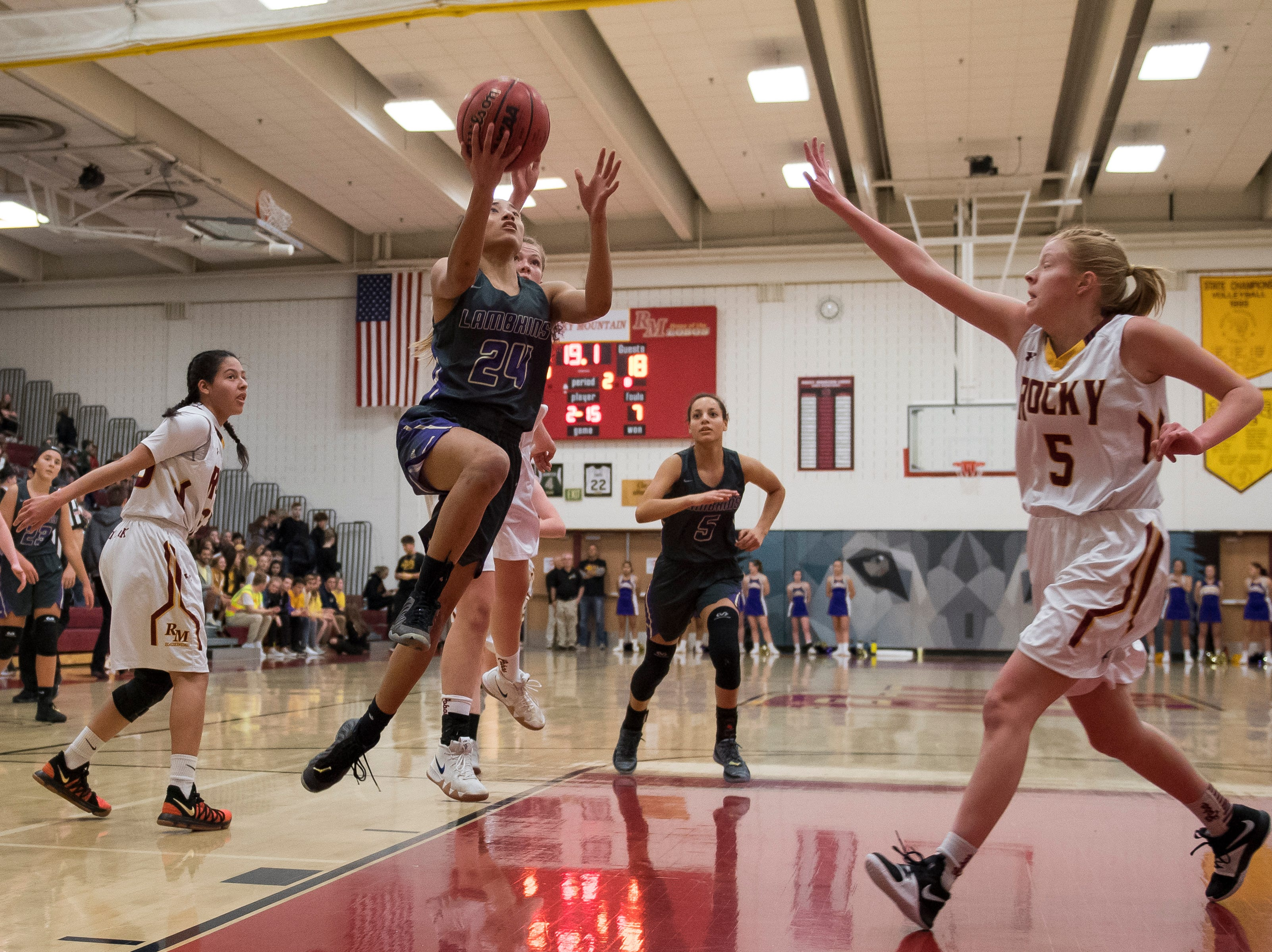 Fort Collins High School senior Isabel Layne (24) goes up for a layup against Rocky Mountain High School senior Chloe Eberl (5) on Friday, Jan. 18, 2019, at Rocky Mountain High School in Fort Collins, Colo.