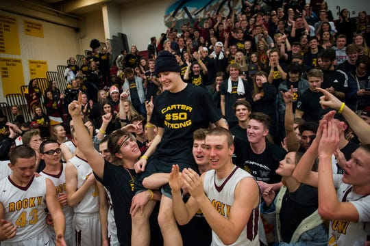 Rocky Mountain High School students hoist up senior Carter Edgerley (50) after a 54-40 win over rival Fort Collins High School on Friday, Jan. 18, 2019, at Rocky Mountain High School in Fort Collins, Colo.