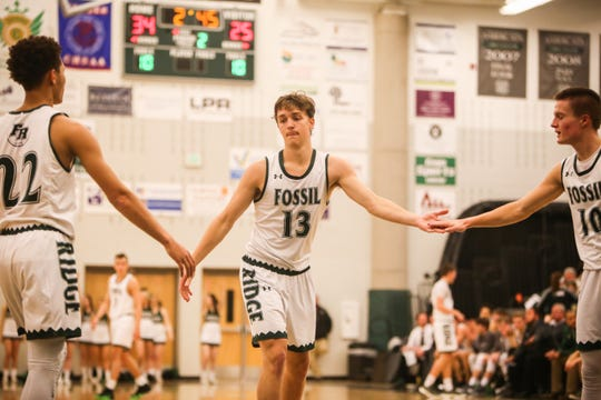 In this file photo, Fossil Ridge basketball player Holdyn Kawcak high fives teammates after making a freethrow in a previous game.