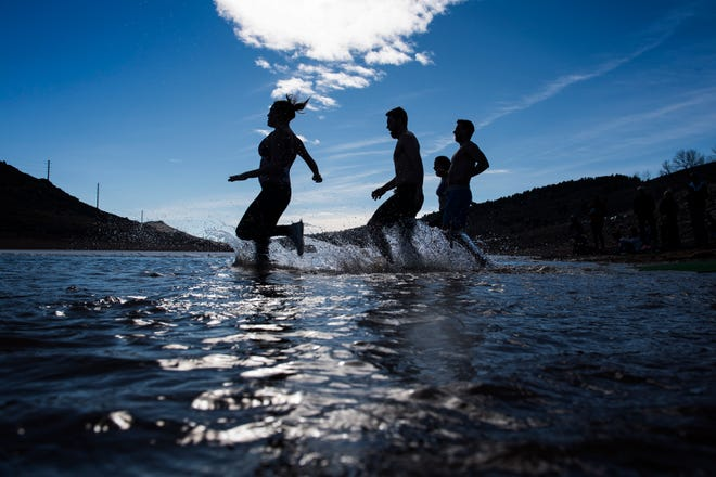 Runners jaunt into Horsetooth Reservoir in Fort Collins, Colo.