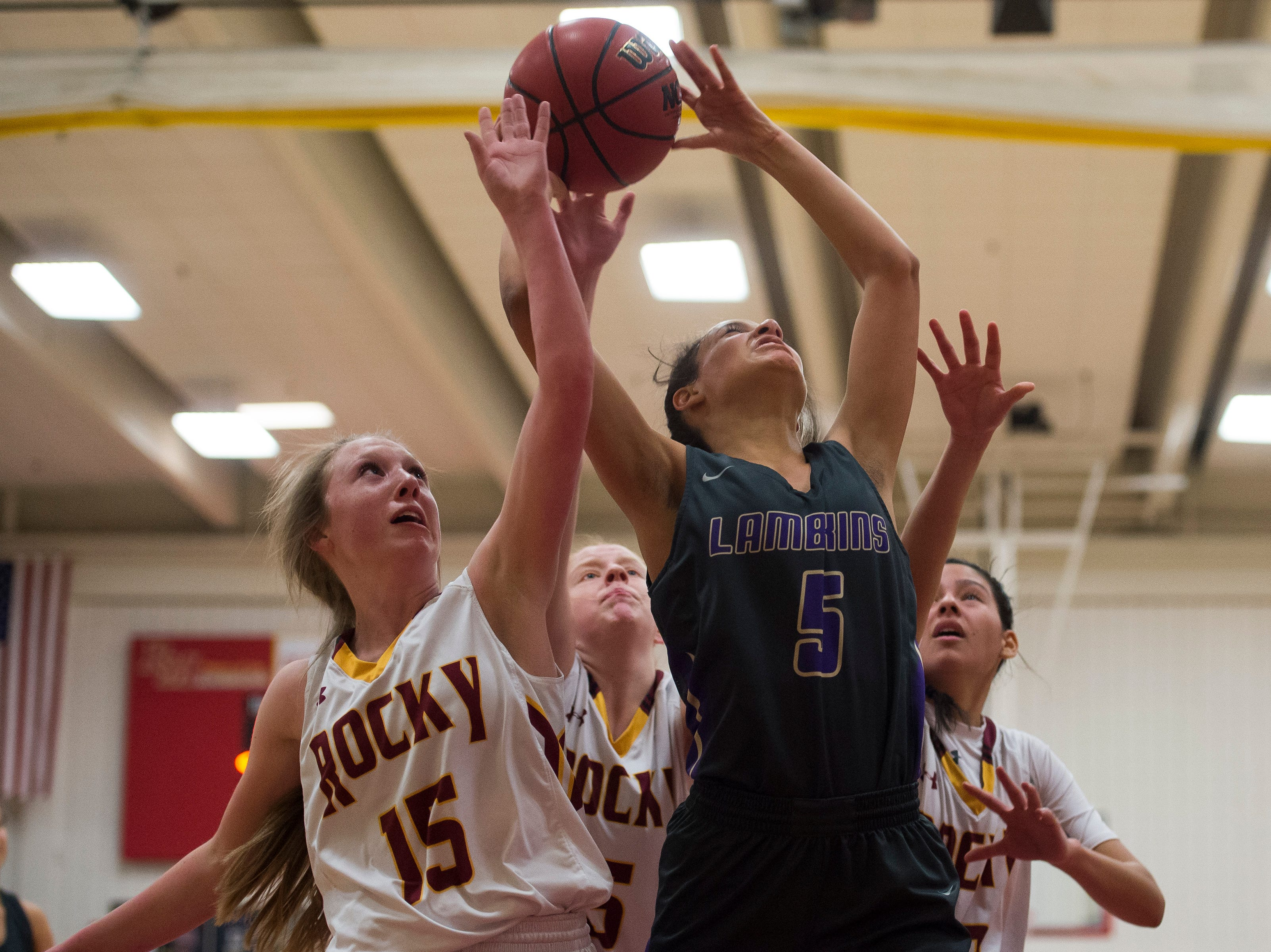 Fort Collins High School senior Hailey Clark (5) attempts  shot over Rocky Mountain High School defenders on Friday, Jan. 18, 2019, at Rocky Mountain High School in Fort Collins, Colo.