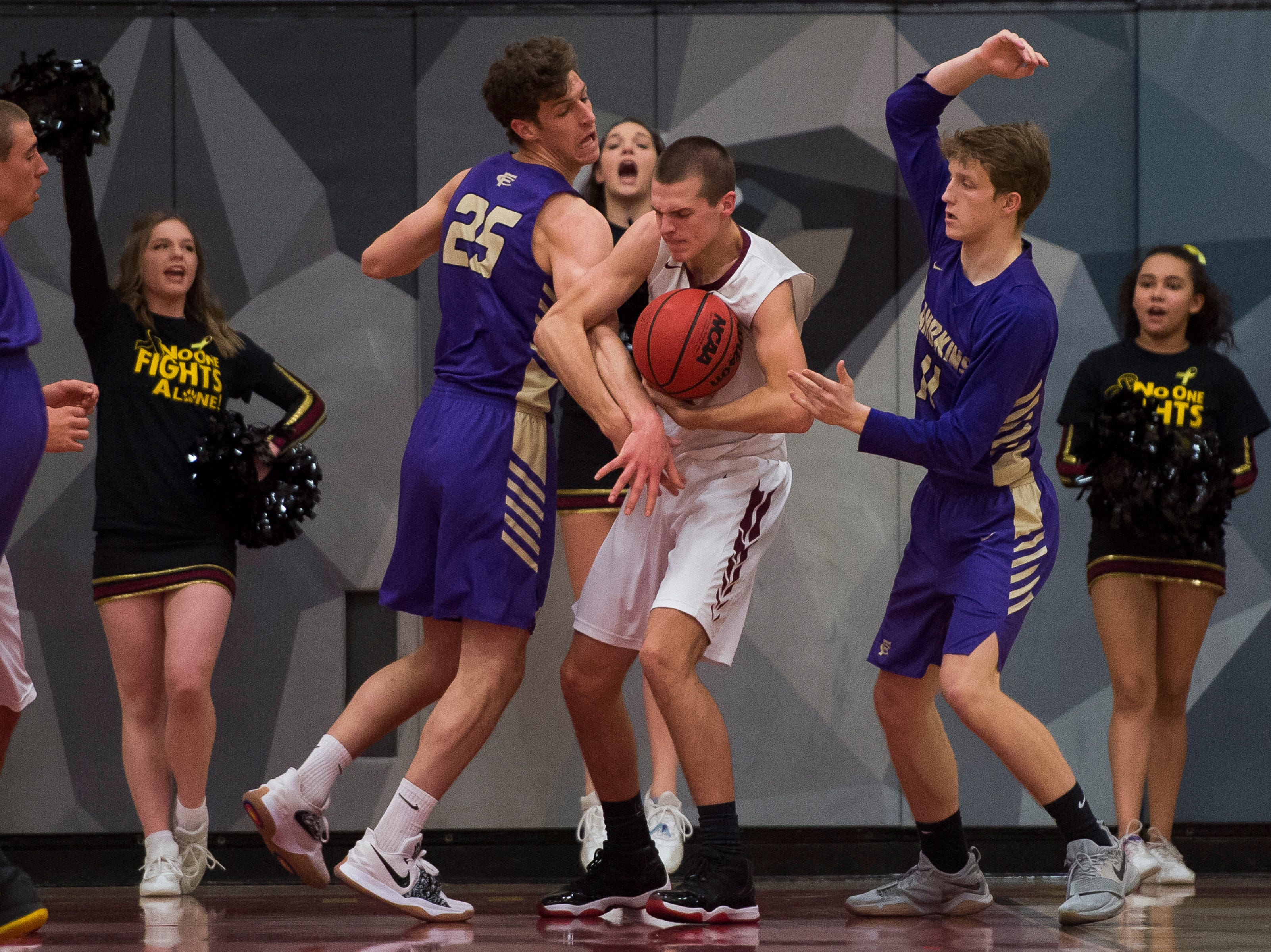 Rocky Mountain High School junior Kenan Schuler (32) and Fort Collins High School senior Benny Khouri (25) struggle for the ball on Friday, Jan. 18, 2019, at Rocky Mountain High School in Fort Collins, Colo.