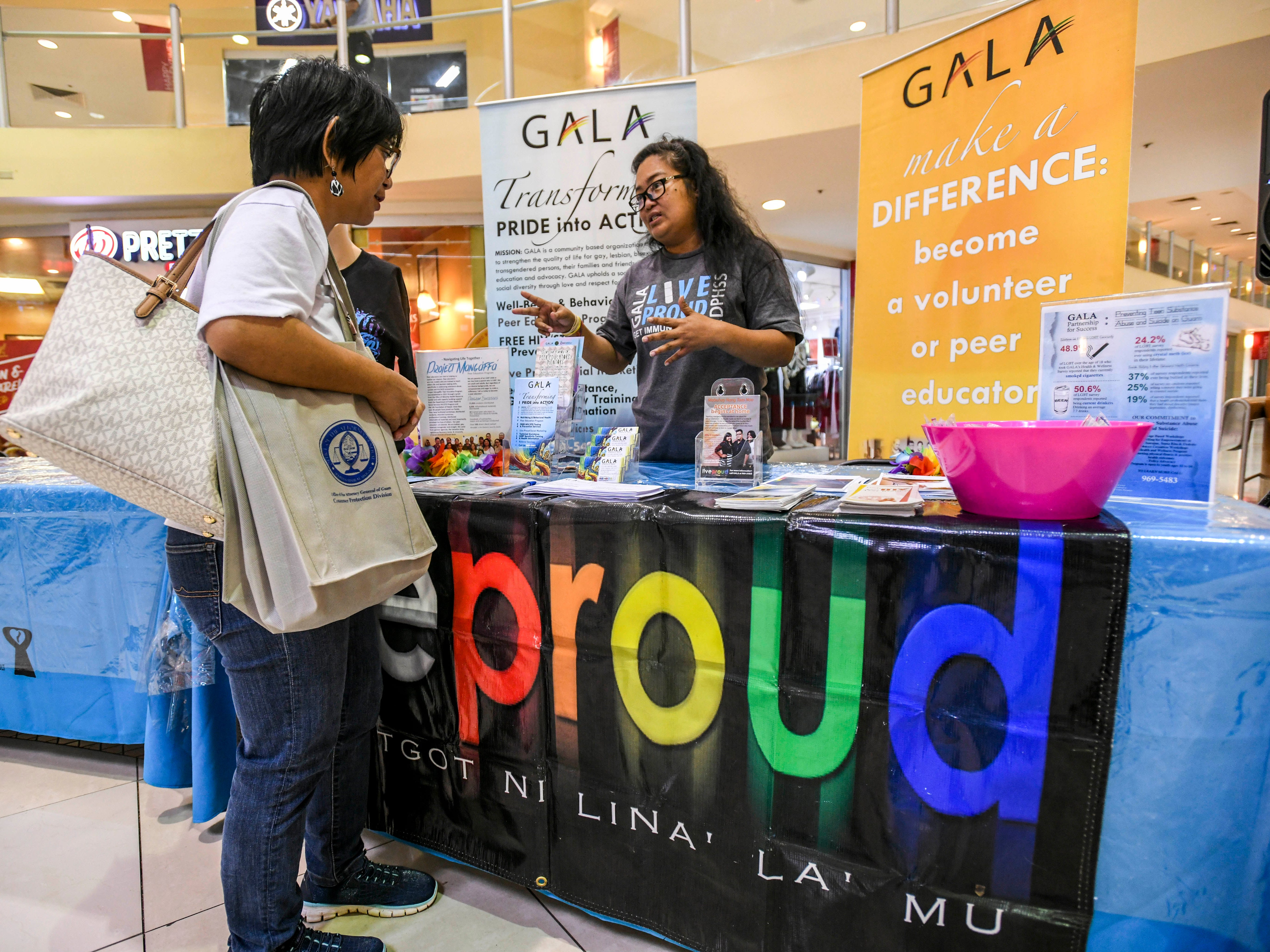 Vicente S.A. Benavente Middle School teacher Marlene Mendiola, left, listens to GALA Project Assistant Flo Mesa during the National Slavery and Human Trafficking Prevention Month and National Stalking Awareness Month Outreach Fair at the Agana Shopping Center on Saturday, Jan. 19, 2019.