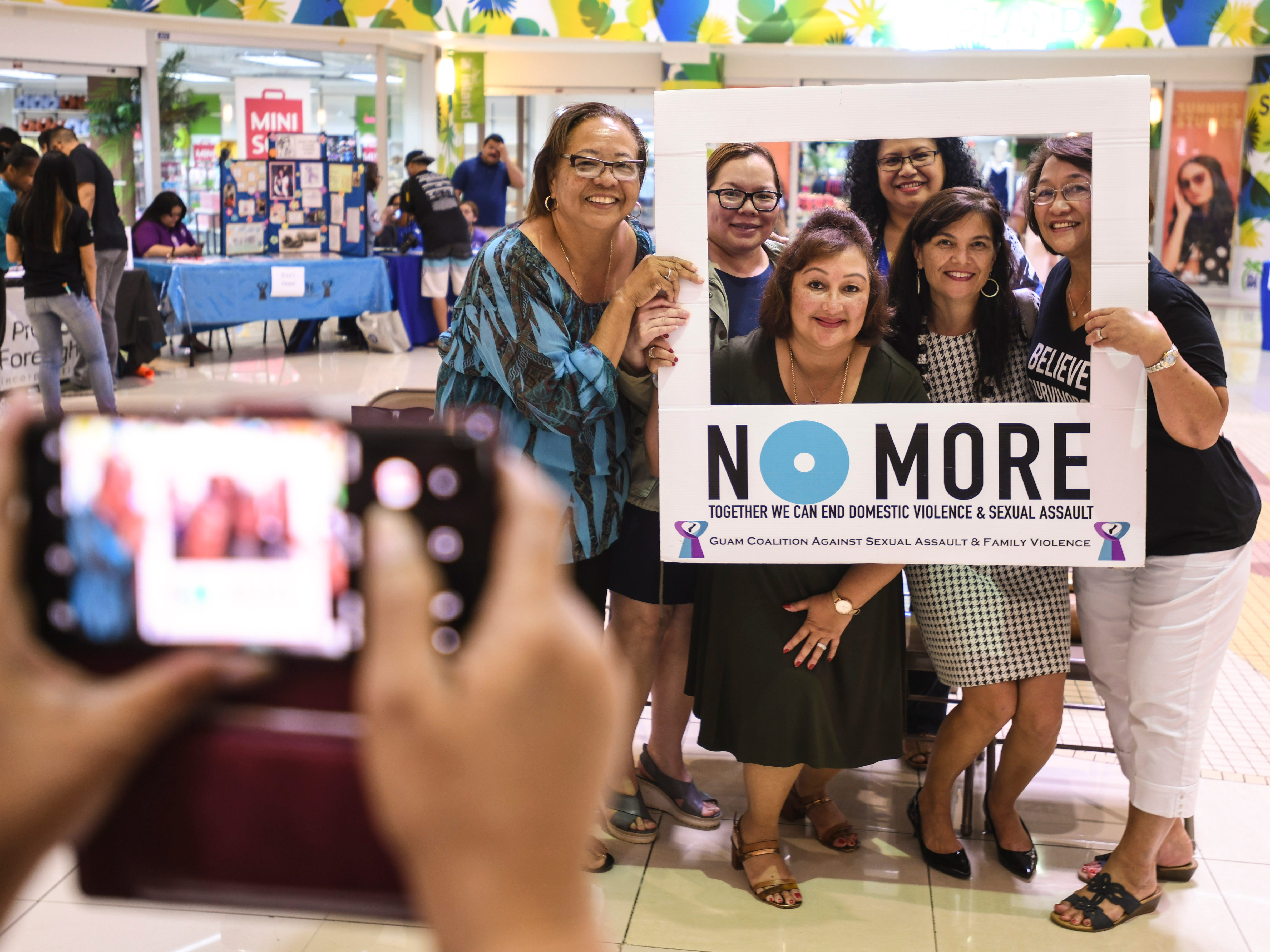 Guam Behavioral Health and Wellness Center Director Therese Arriola, Sen. Therese Terlaje and other gather for a photo during the National Slavery and Human Trafficking Prevention Month and National Stalking Awareness Month Outreach Fair at the Agana Shopping Center on Saturday, Jan. 19, 2019.