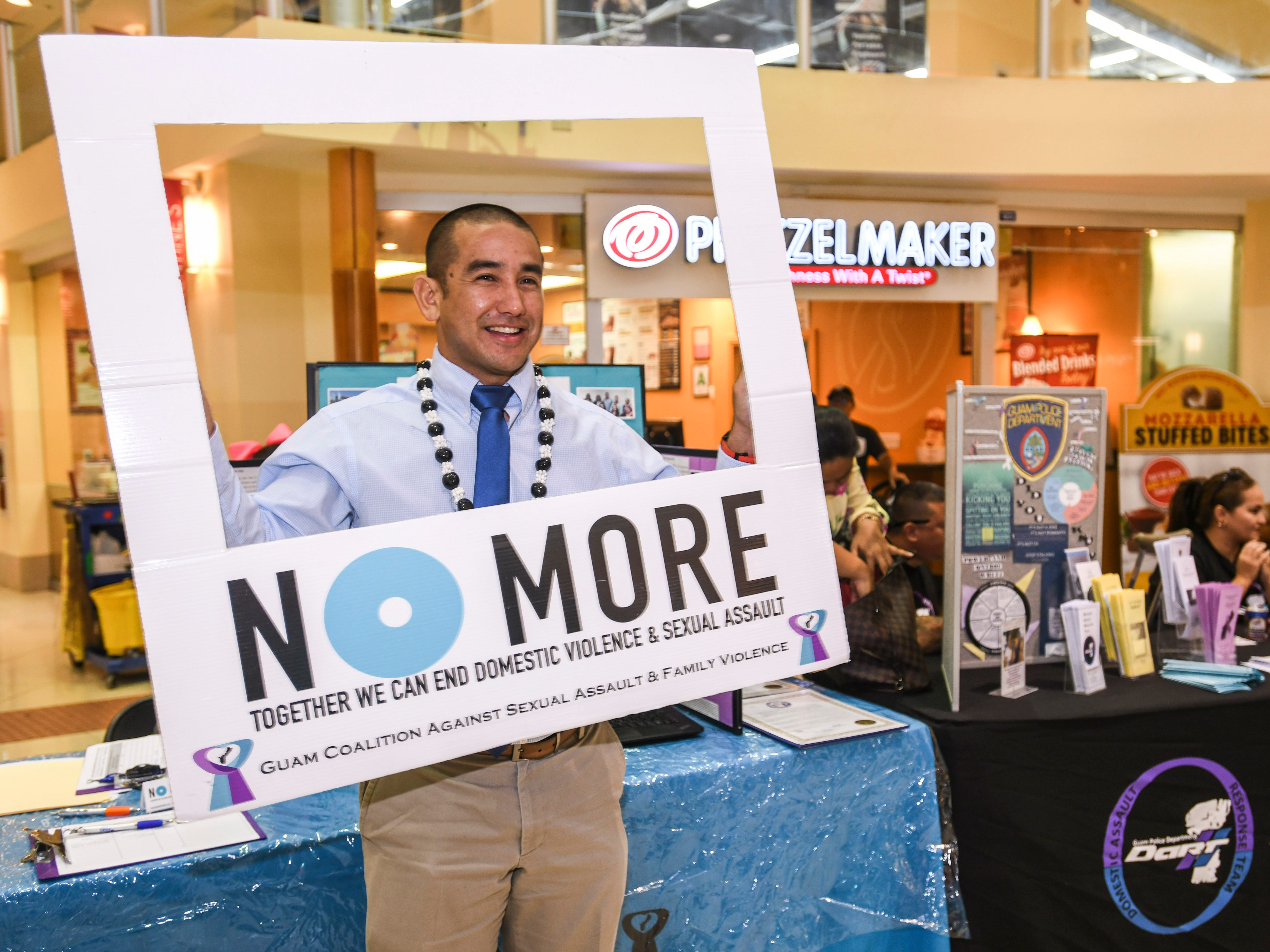 Leevin Camacho, Attorney General of Guam, obliges himself for a photo while visiting the Guam Coalition Against Sexual Assault and Family Violence table during the National Slavery and Human Trafficking Prevention Month and National Stalking Awareness Month Outreach Fair at the Agana Shopping Center on Saturday, Jan. 19, 2019.