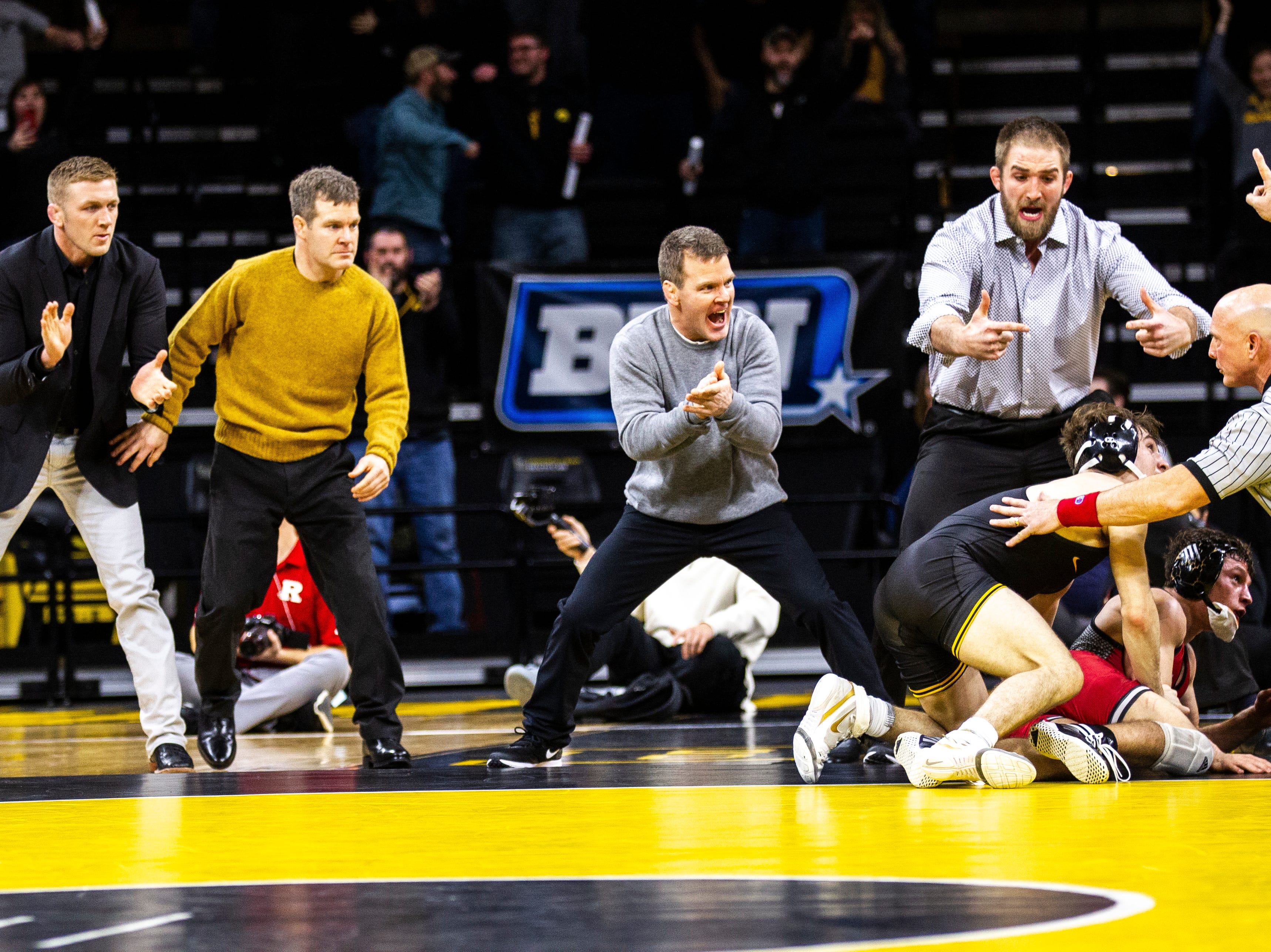 Iowa's Ryan Morningstar, head coach Tom Brands, Terry Brands, and Bobby Telford celebrate after Iowa's Austin DeSanto scored a takedown on Rutgers' Nick Suriano at 133 during a NCAA Big Ten Conference wrestling dual on Friday, Jan. 18, 2019, at Carver-Hawkeye Arena in Iowa City, Iowa.