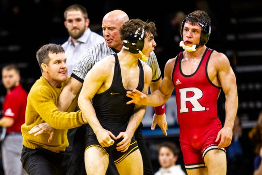 Iowa's Austin DeSanto, left, gets held back by Iowa head coach Tom Brands after DeSanto scored a takedown to win a decision over Rutgers' Nick Suriano at 133 during a NCAA Big Ten Conference wrestling dual on Friday, Jan. 18, 2019, at Carver-Hawkeye Arena in Iowa City, Iowa.