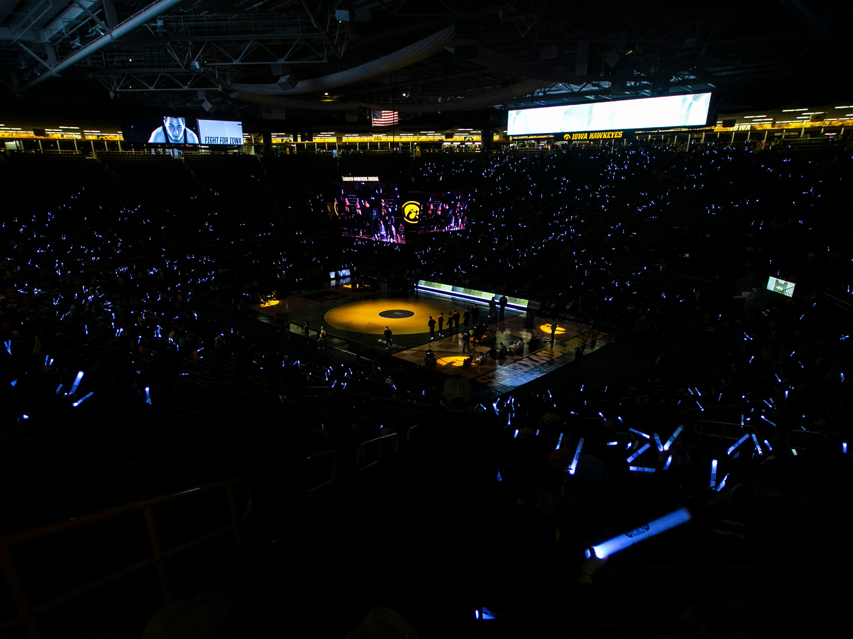 Fans wave glow-sticks before a NCAA Big Ten Conference wrestling dual on Friday, Jan. 18, 2019, at Carver-Hawkeye Arena in Iowa City, Iowa.