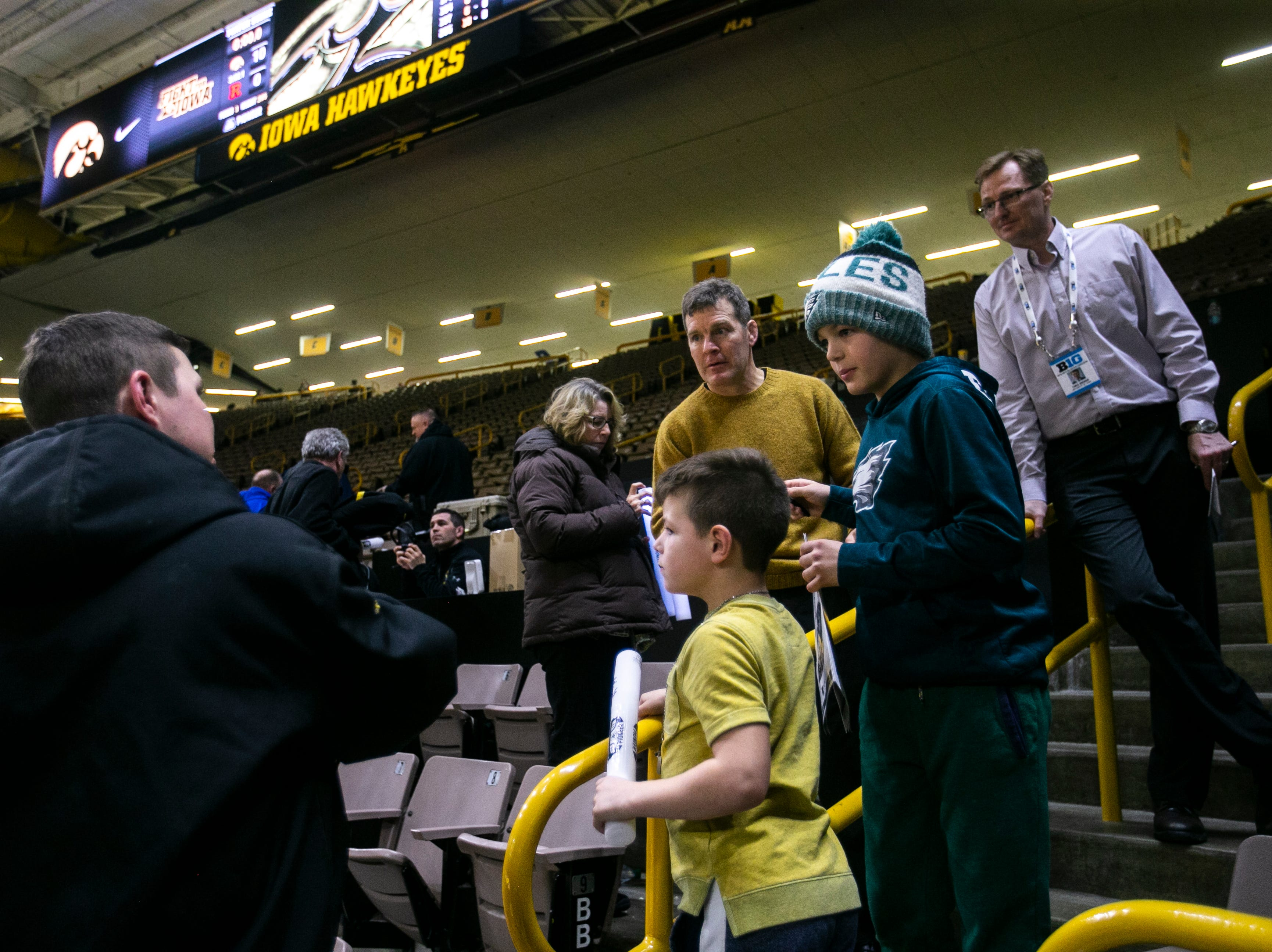 Iowa head coach Tom Brands signs autographs for fans after a NCAA Big Ten Conference wrestling dual on Friday, Jan. 18, 2019, at Carver-Hawkeye Arena in Iowa City, Iowa.