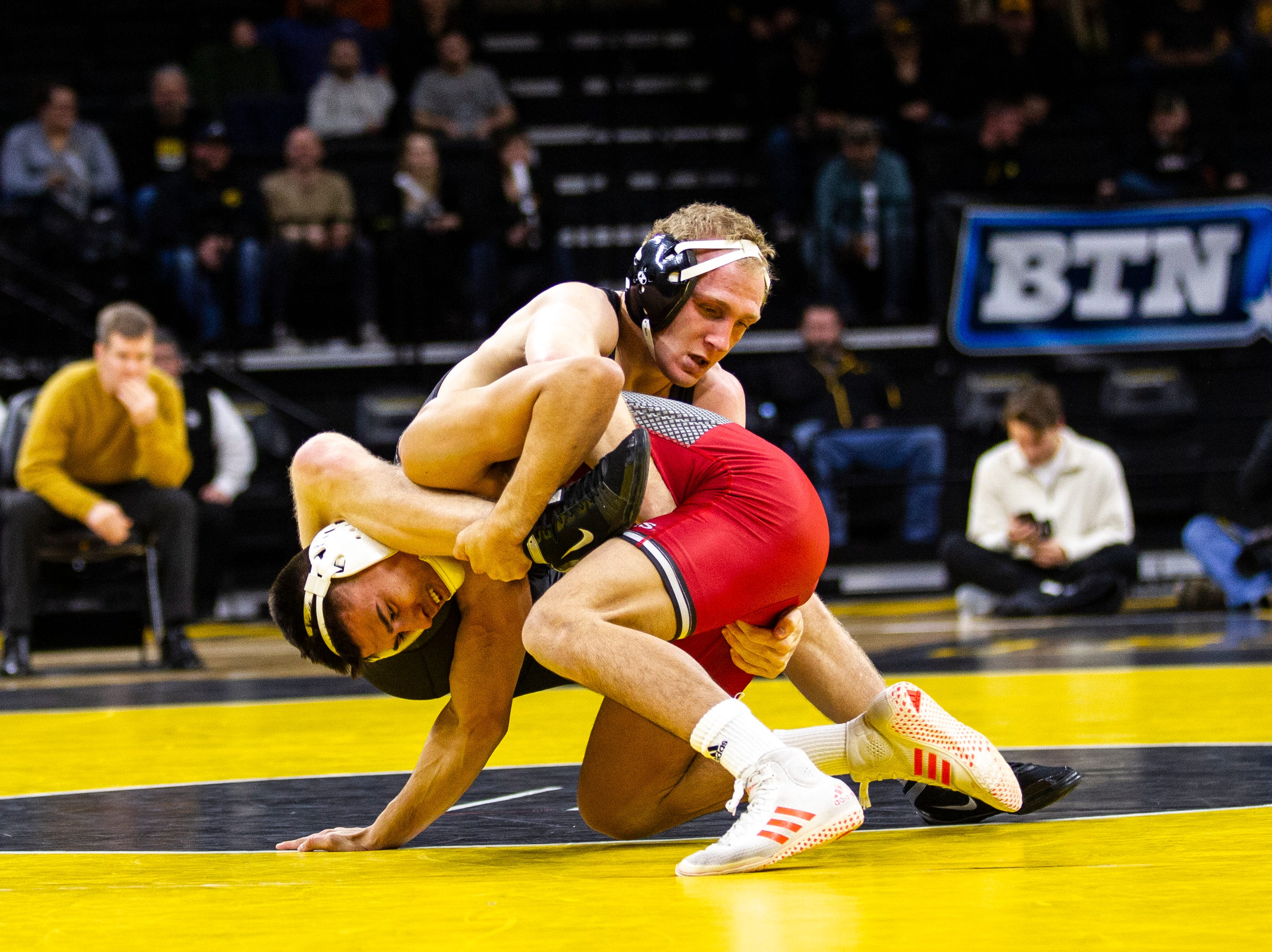 Iowa's Kaleb Young, top, wrestles Rutgers' John Van Brill at 157 during a NCAA Big Ten Conference wrestling dual on Friday, Jan. 18, 2019, at Carver-Hawkeye Arena in Iowa City, Iowa.