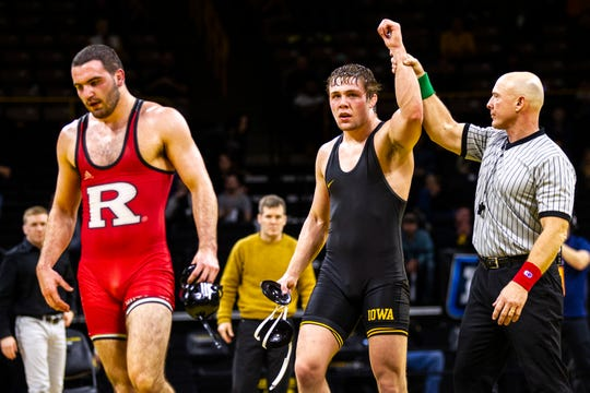 Iowa's Jacob Warner, center, has his hand raised after scoring a decision over Rutgers' Matthew Correnti at 197 during a NCAA Big Ten Conference wrestling dual on Friday, Jan. 18, 2019, at Carver-Hawkeye Arena in Iowa City, Iowa.